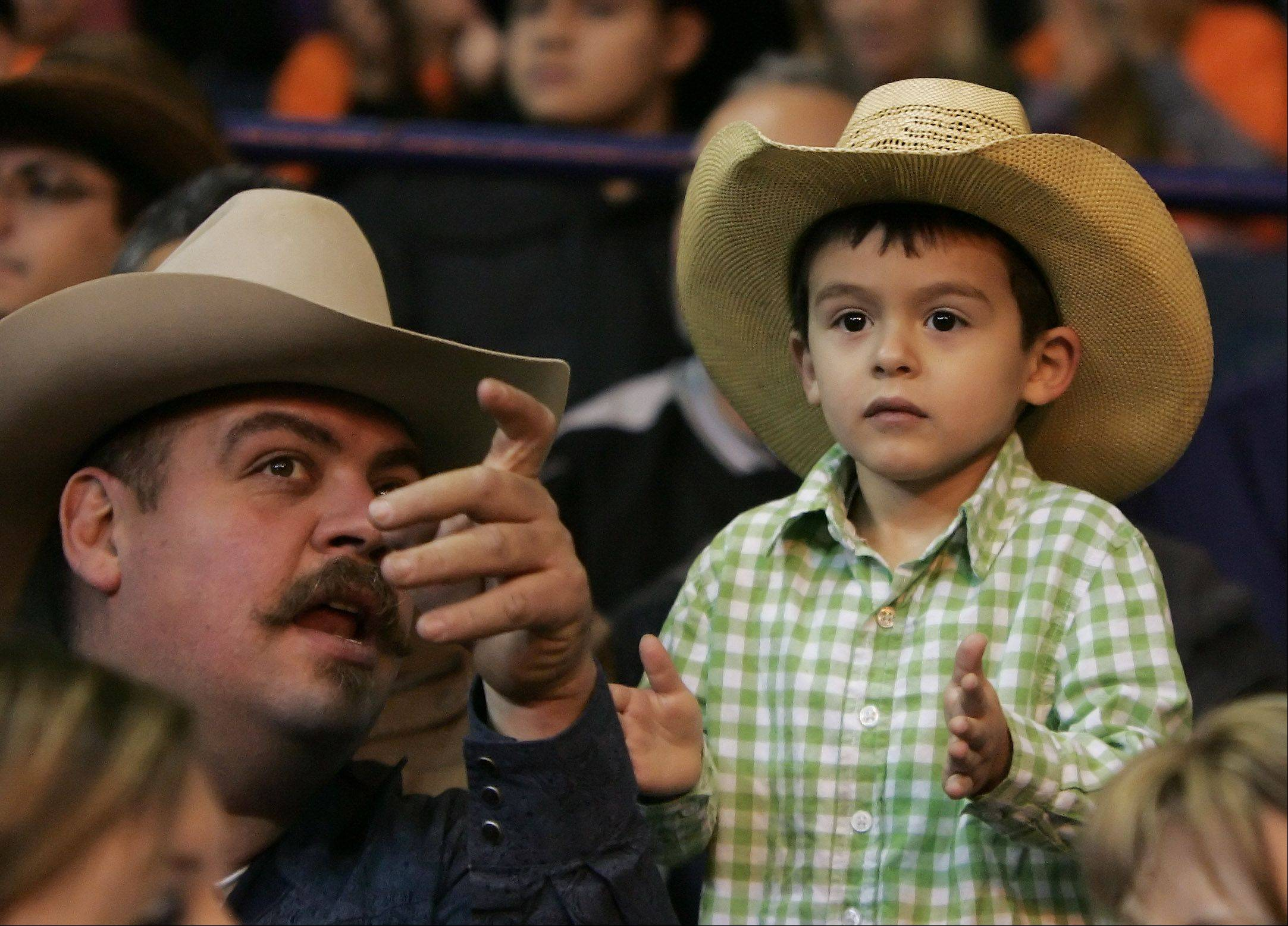 Lazaro Quloa, 3, of Joliet, watches the bull riders with his father, Jose, during the Professional Bull Riders Chicago Invitational Sunday at the Allstate Arena in Rosemont. Riders from around the world competed in the arena by riding 2,000-pound bulls.