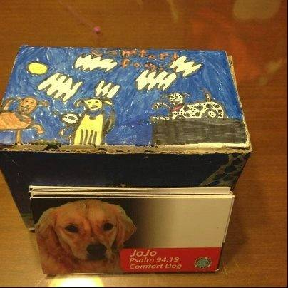 The 6-year-old girl who colored this box to hold cards for each of the visiting comfort dogs was one of seven students from Victoria Soto's class to survive the attack after hiding in a closet, comfort dog handler George Shiestel of Arlington Heights said.