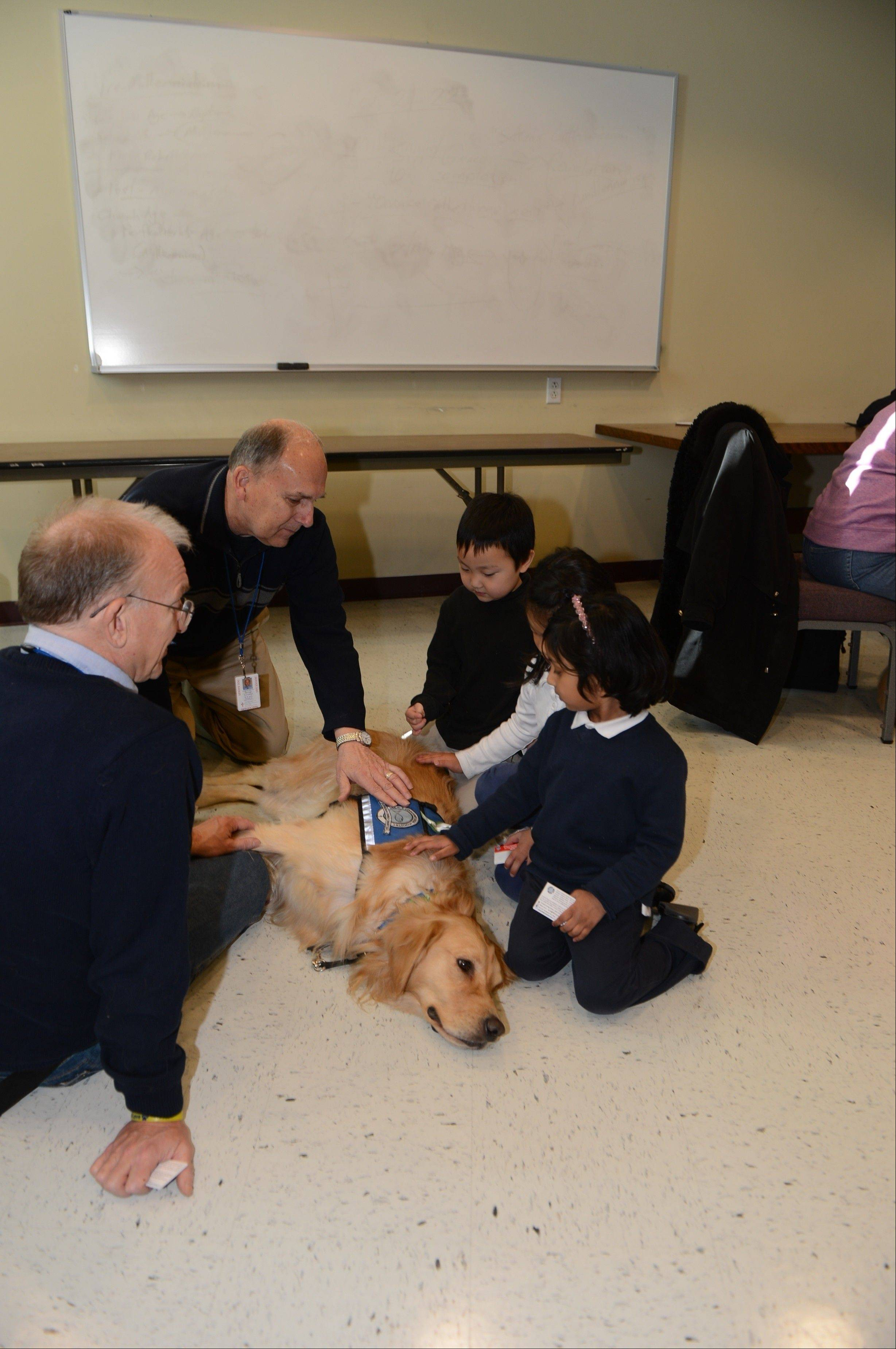Pastor Paul Klopke, left, of Living Christ Lutheran Church in Arlington Heights, George Schiestel of Arlington Heights and comfort dog JoJo visit with children at the Lutheran school in Danbury, Conn., this month following the school shootings in nearby Newtown. They also visited children who were in the school where the shootings occurred.