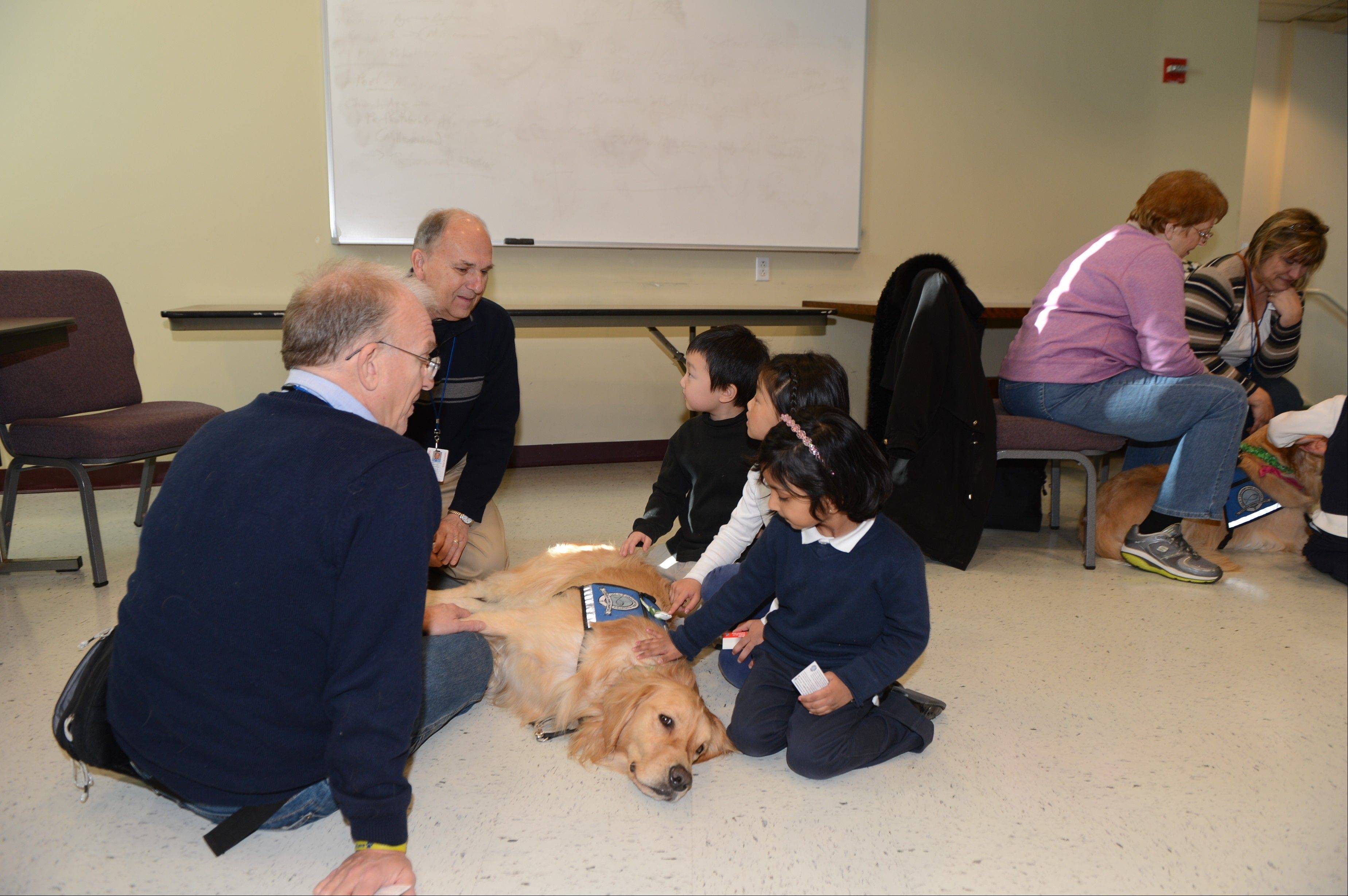 Pastor Paul Klopke, left, of Living Christ Lutheran Church in Arlington Heights, George Schiestel of Arlington Heights and comfort dog JoJo visit with children at the Lutheran school in Danbury, Conn., this month following the school shootings in nearby Newtown. ----