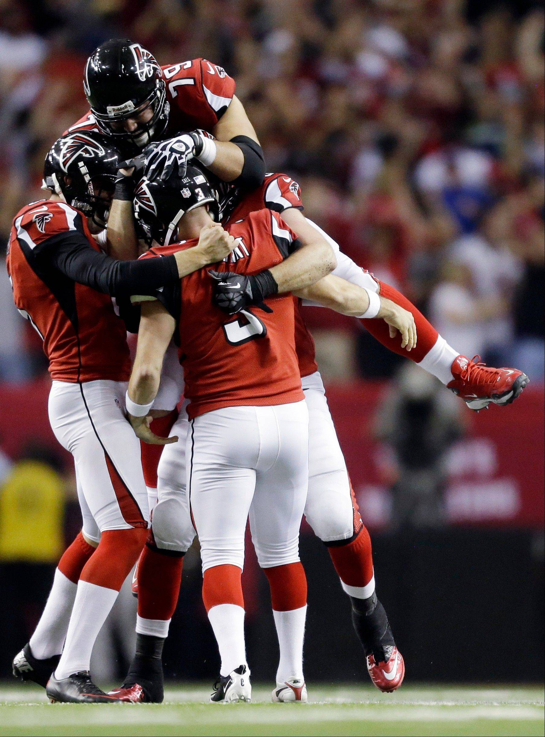 Atlanta Falcons kicker Matt Bryant is congratulated by teammates after making the game-winning field goal during the second half of an NFC divisional playoff NFL football game against the Seattle Seahawks Sunday, Jan. 13, 2013, in Atlanta. The Falcons won 30-28.
