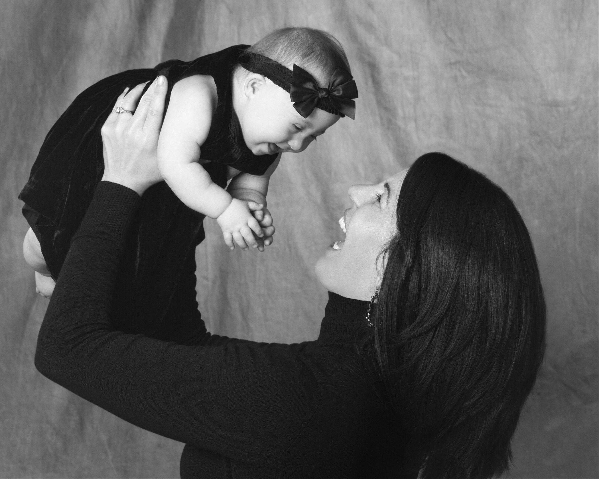 "Charlotte Jablonski, of Johnsburg, is held up by her mom in one of the portraits in ""One Million Voices,"" a photo exhibit opening Tuesday at Woodfield Mall. The exhibit aims to raise awareness about children with Down syndrome."