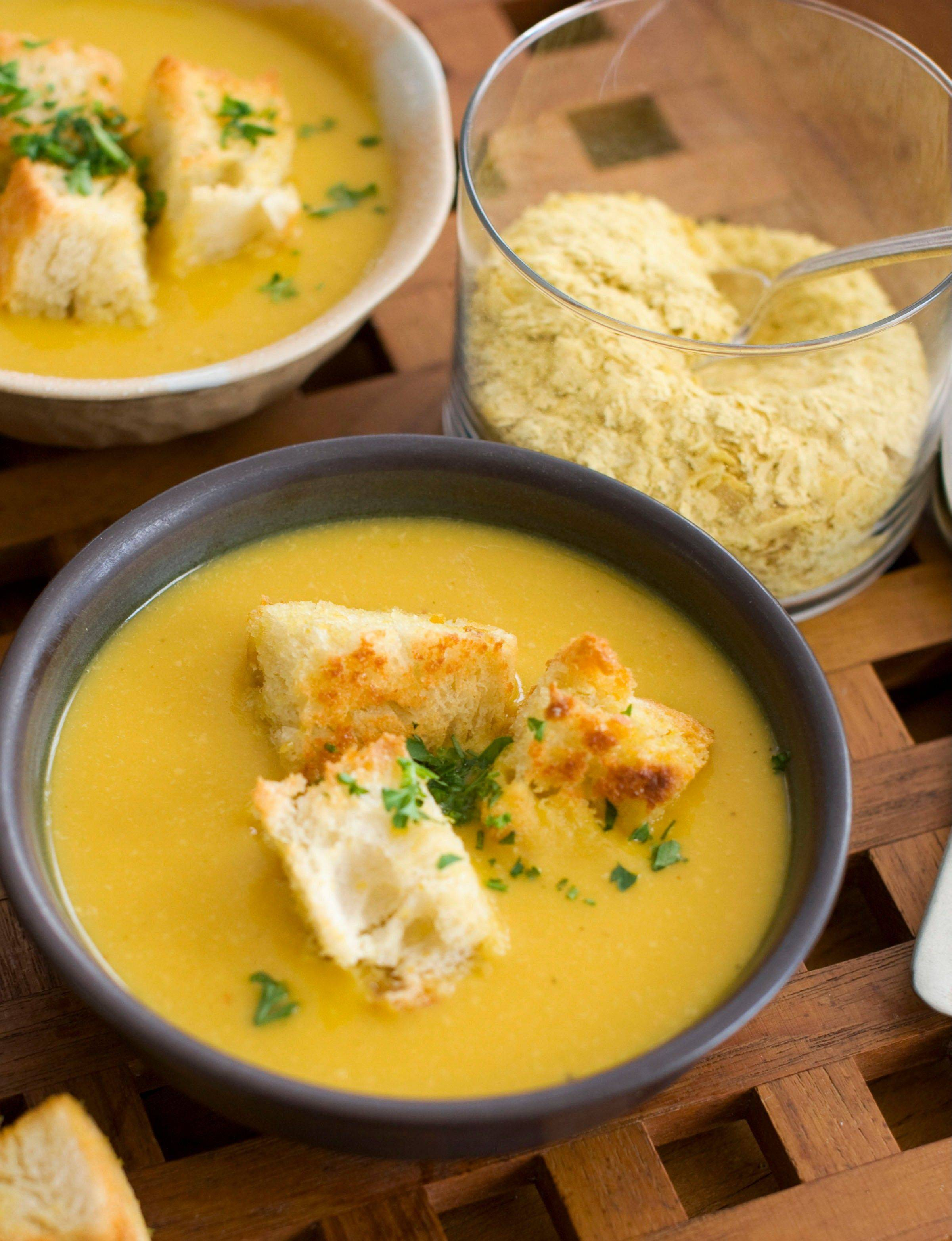 Nutritional yeast flakes lend a savory, cheesy flavor to pumpkin and white bean soup. The flakes season the soup and the sourdough croutons.