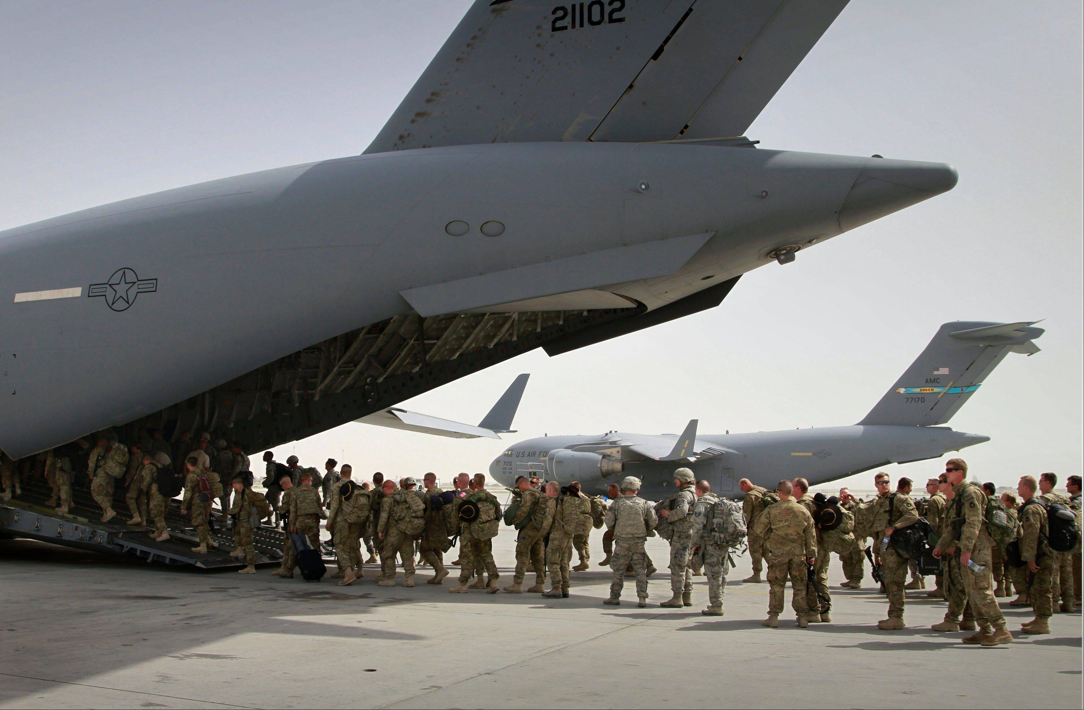 U.S. soldiers board a U.S. military plane, as they leave Afghanistan, at the U.S. base in Bagram north of Kabul, in 2011. Suicides in the U.S. military surged to a record 349 last year, far exceeding American combat deaths in Afghanistan.