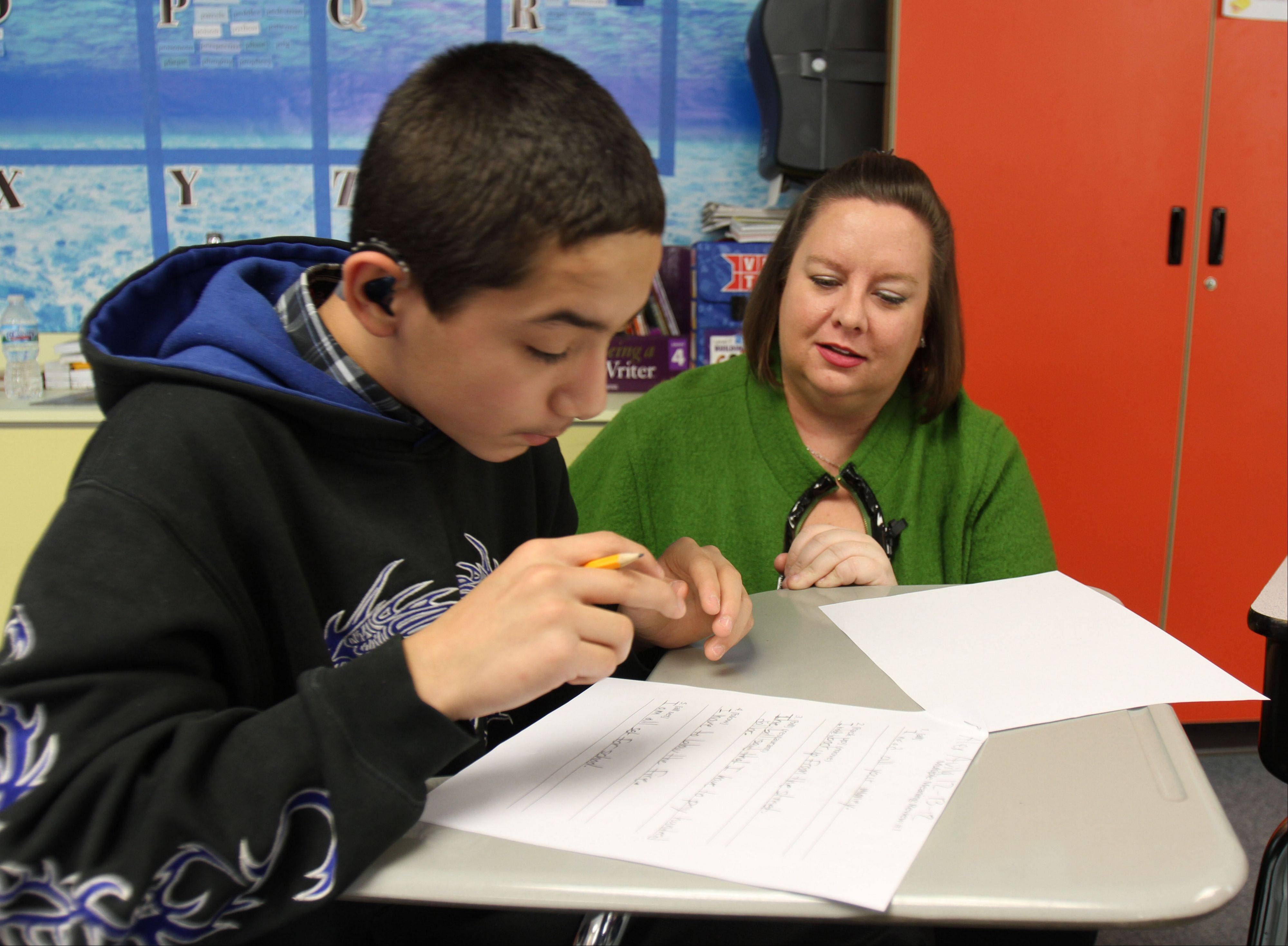 Abigail Currie, right, works on a language assignment with sixth-grader Alex Aliva in her class at the John Powers Center in Vernon Hills.