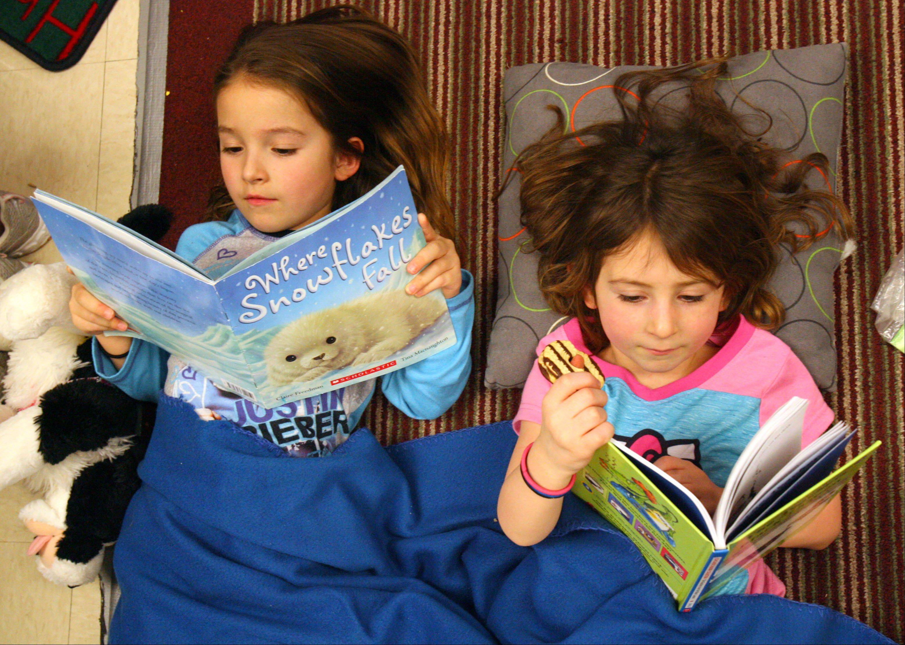 First grade students Daniela Warrensford, left, and Katie Polisson read in their pajamas as Hawthorn Elementary South held their Read 2013 marathon, reading for 2,013 seconds Friday in Vernon Hills.