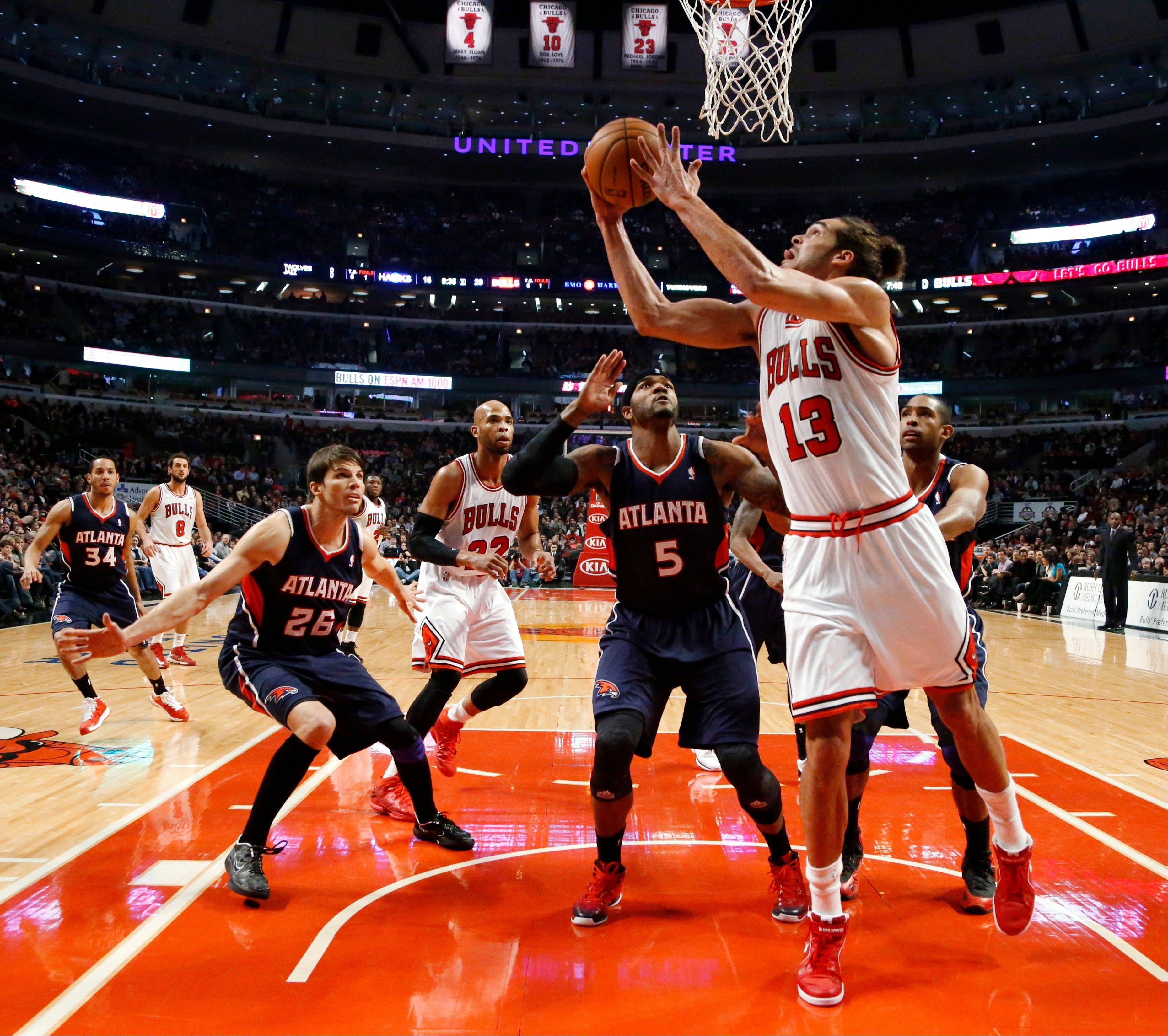 Chicago Bulls center Joakim Noah (13) shoots a reverse layup past Atlanta Hawks' Kyle Korver (26) and Josh Smith (5) during the first half of an NBA basketball game Monday, Jan. 14, 2013, in Chicago.