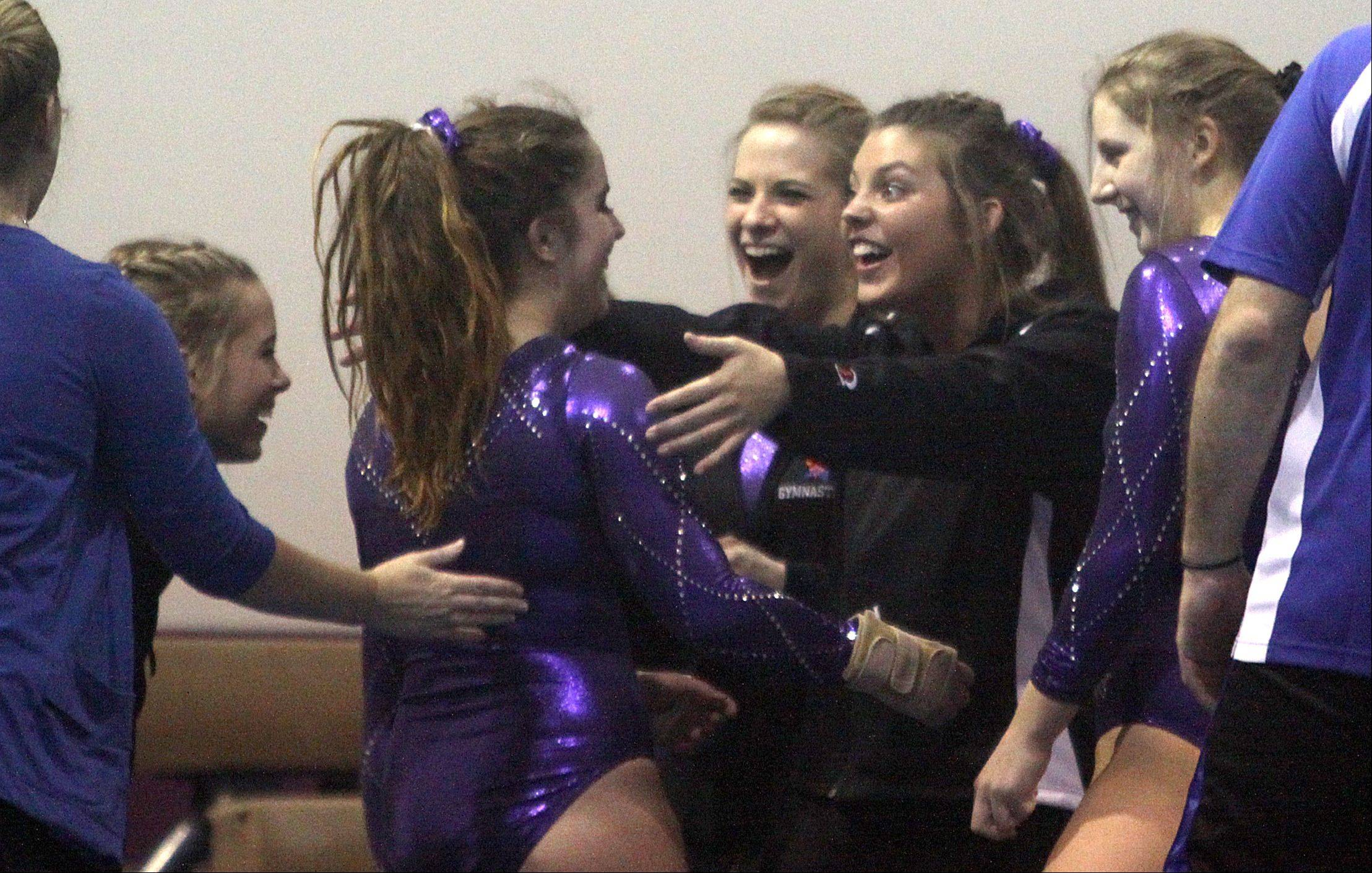 St. Charles co-op gymnasts congratulate teammate Alix Scherer, center, after Scherer completed a beam routine during a gymnastics meet at St. Charles Gymnastics Academy on Monday night.
