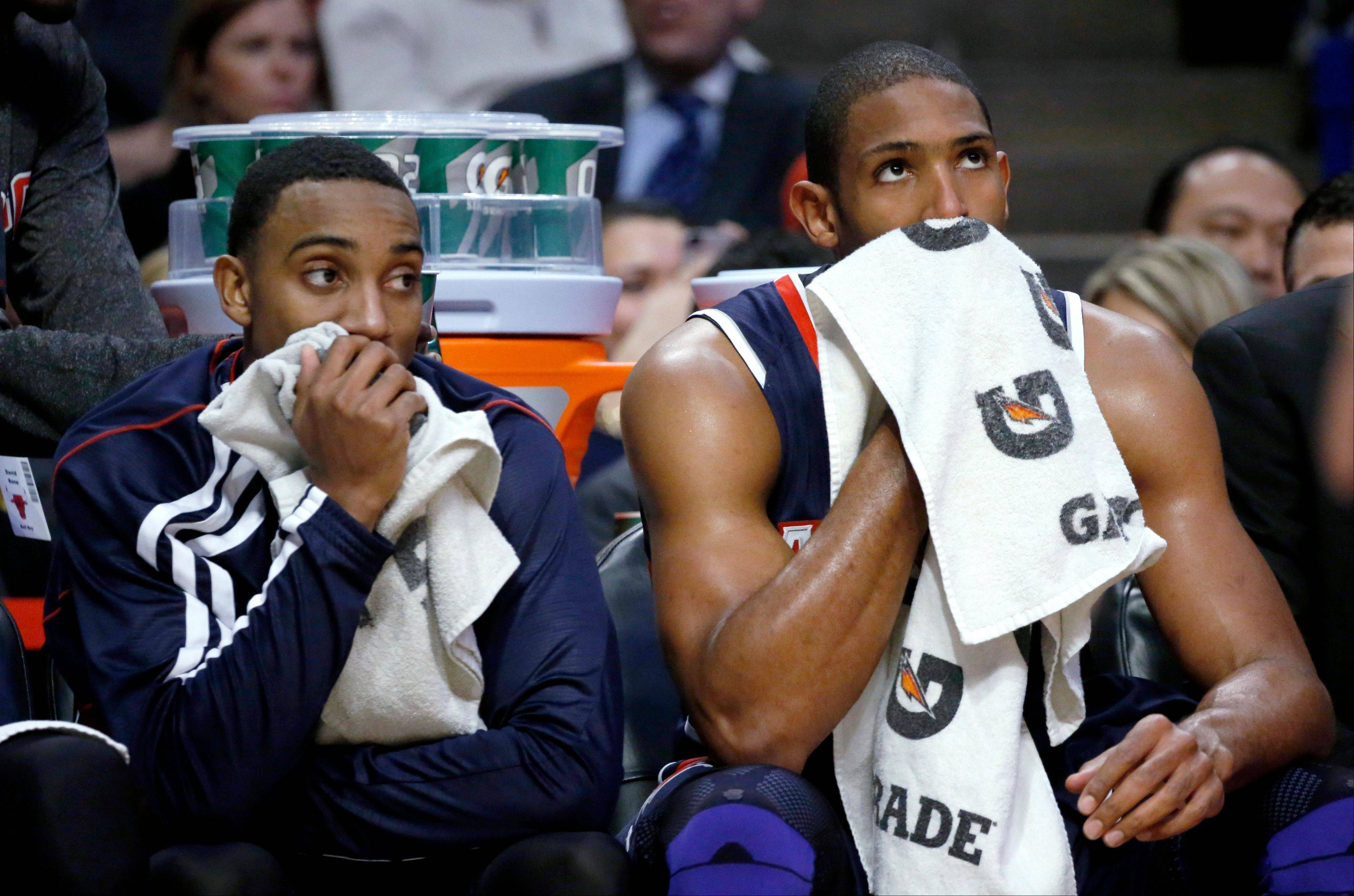 Atlanta Hawks' Jeff Teague, left, and Al Horford sit on the bench during the second half of an NBA basketball game against the Chicago Bulls on Monday, Jan. 14, 2013, in Chicago. The Bulls won 97-58.