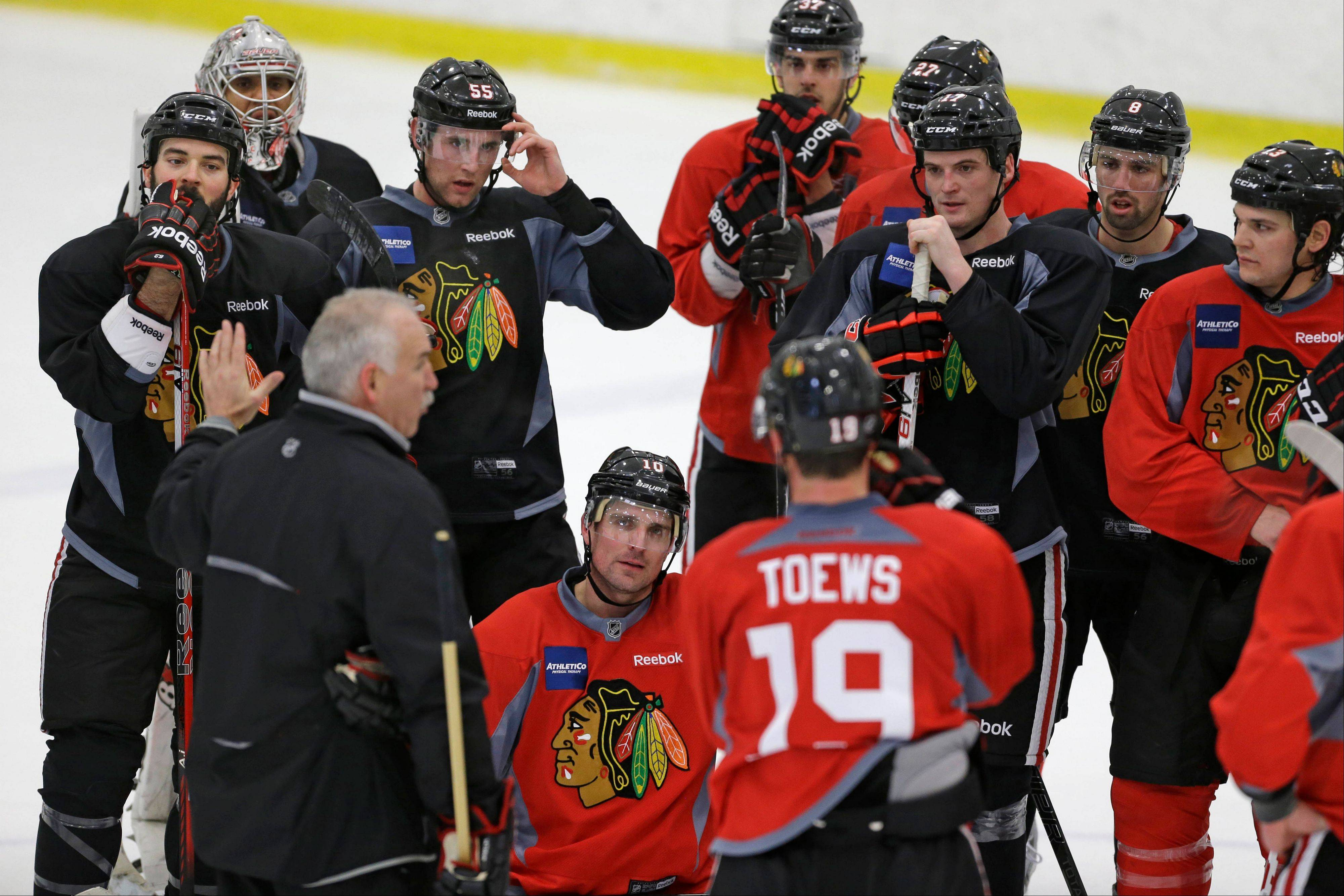 Blackhawks coach Joel Quenneville, bottom left, speaks to his team during Monday's practice.