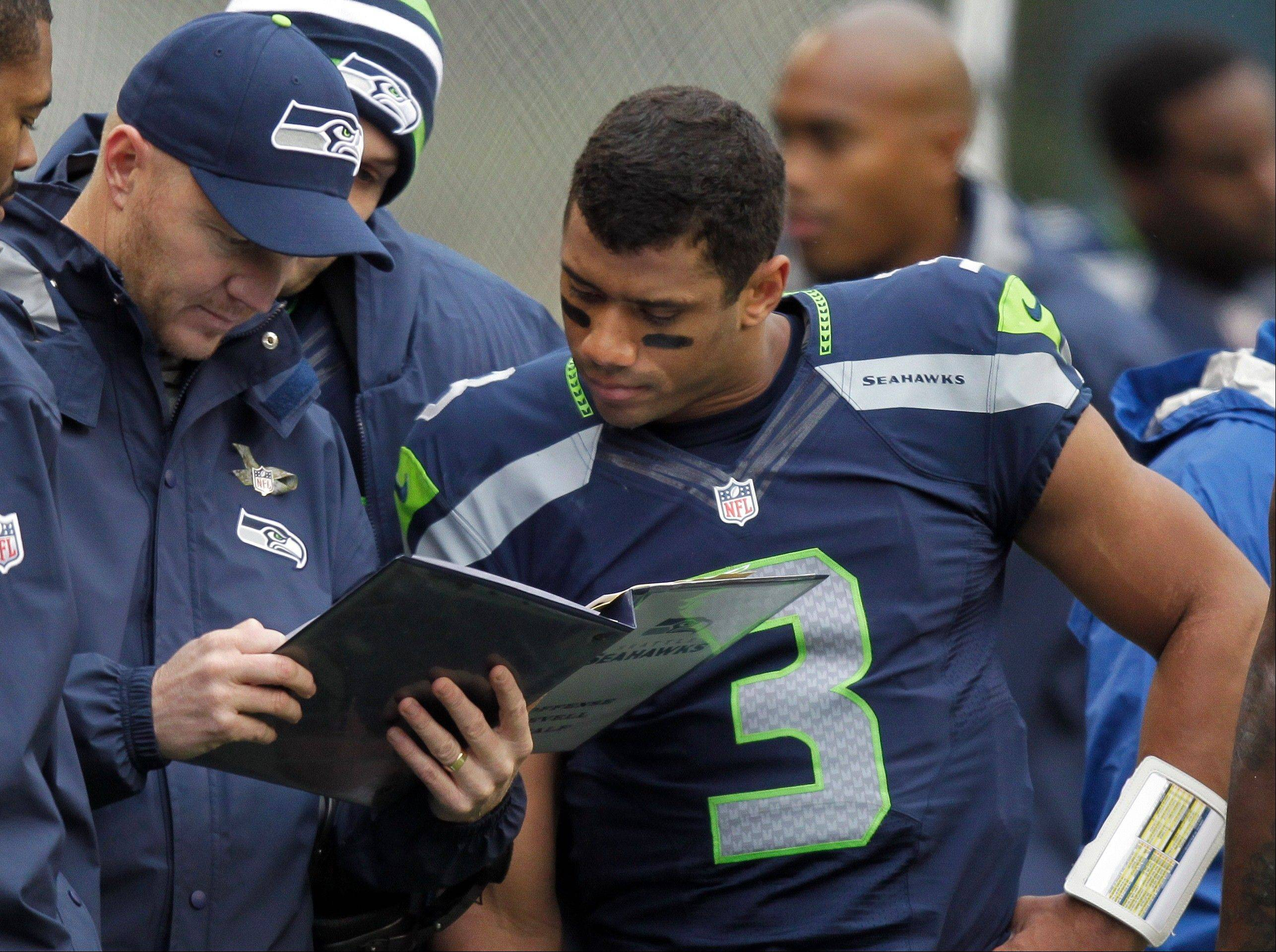 Seattle Seahawks quarterback Russell Wilson, right, looks at a playbook with offensive coordinator Darrell Bevell, left, on the sidelines during the first half of an NFL football game against the New York Jets in Seattle.