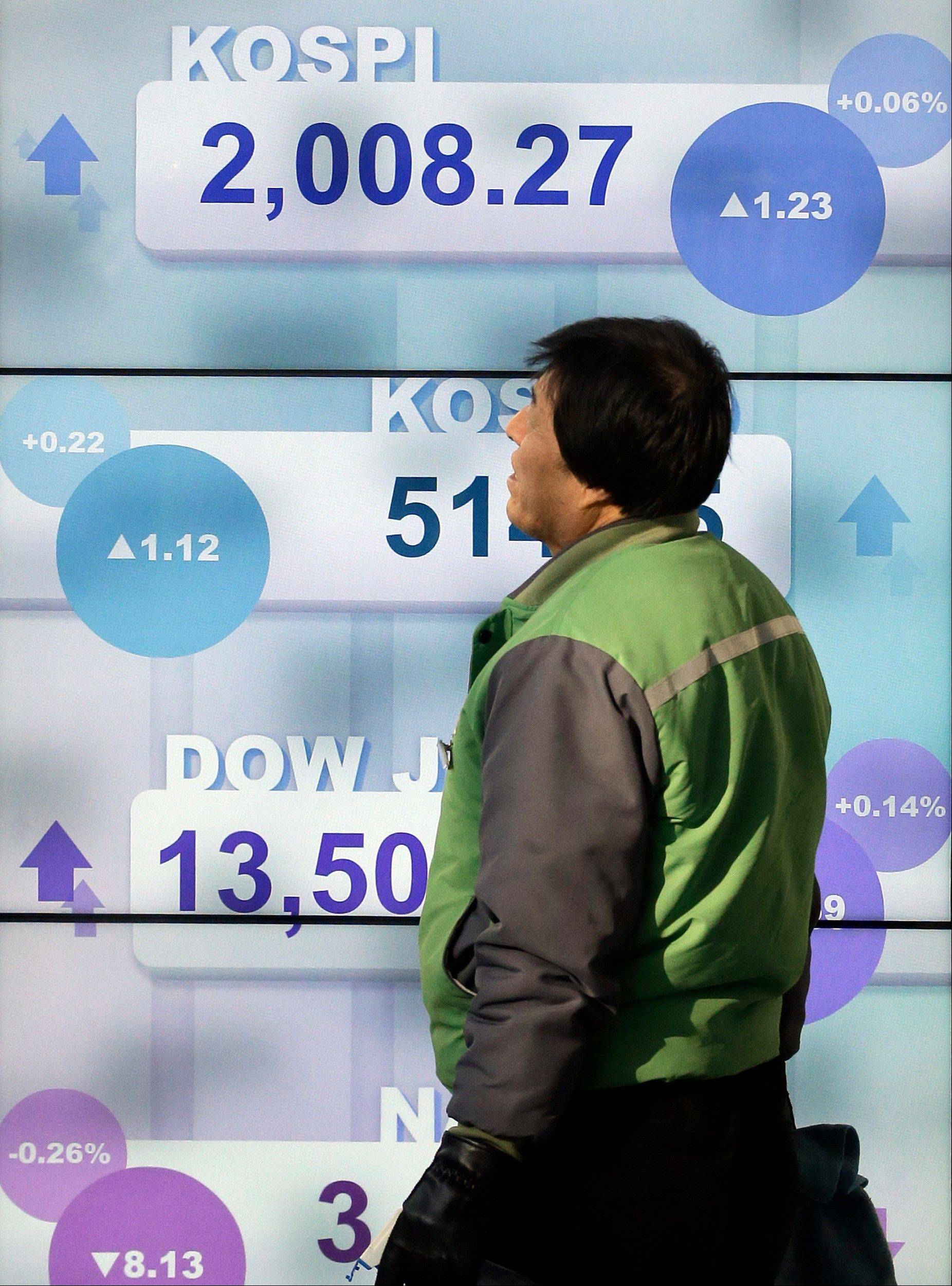 A man walks by a screen showing the Korea Composite Stock Price Index (KOSPI) in downtown Seoul, South Korea, Tuesday.