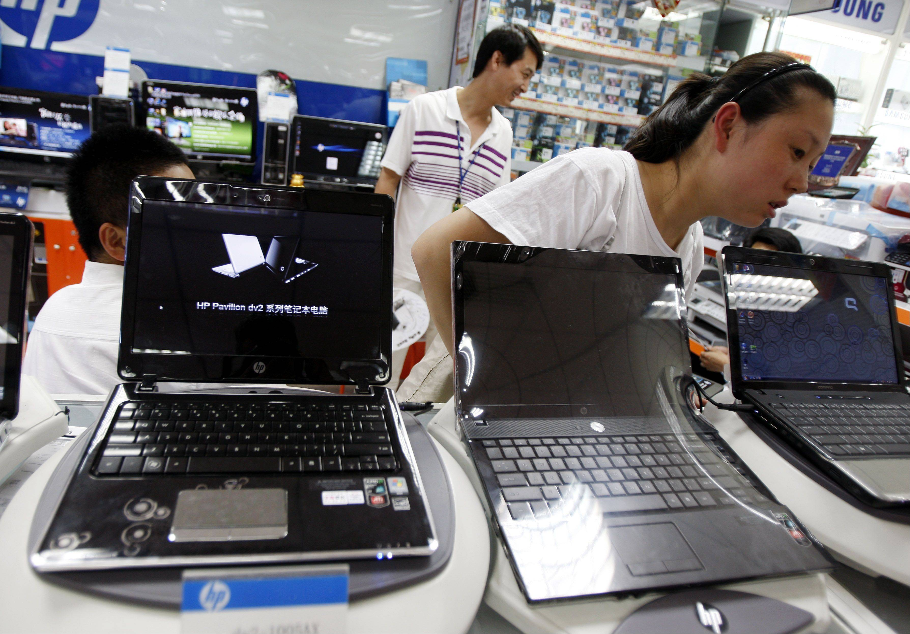 Sales staff stand behind computers in a store in Beijing, China.