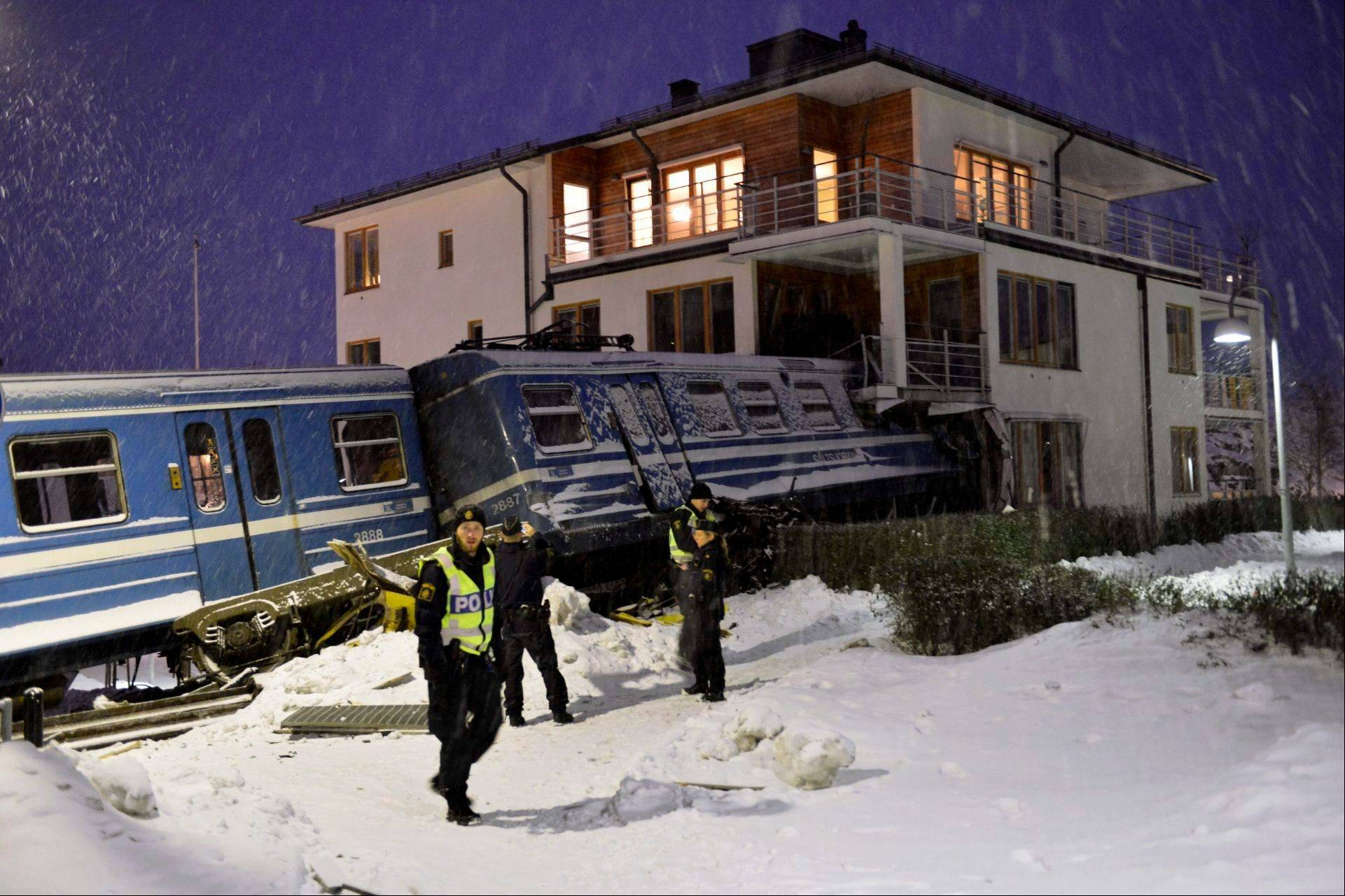 Emergency services attend the scene after a derailed train crashed into the side of a residential building in Saltsjobaden outside Stockholm, Tuesday Jan, 15, 2013. A woman obtained the keys to the train and drove it away before it crashed into the building. The woman was injured in the incident and there are no reports of injuries of people in the building.