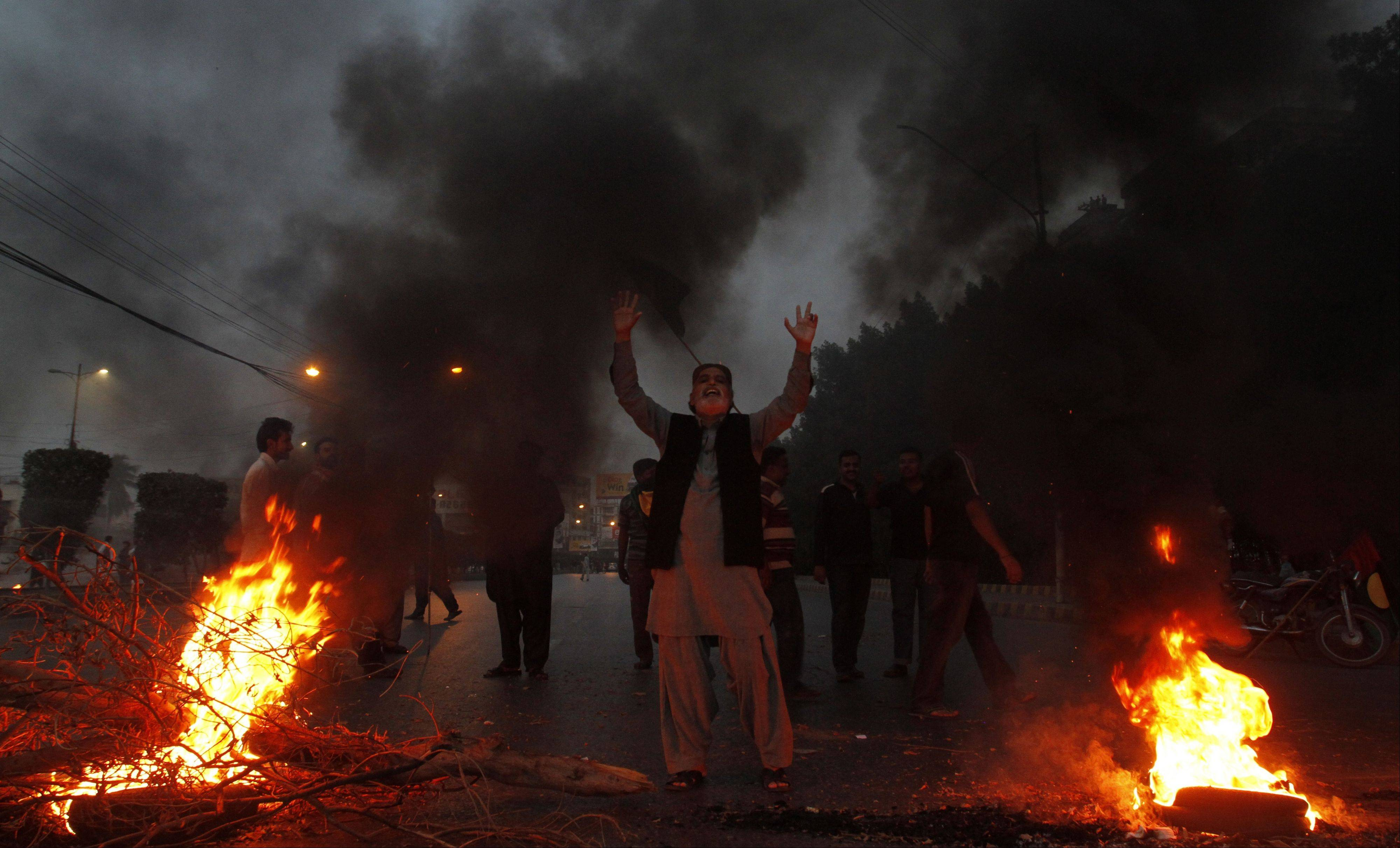 Supporters of Pakistan�s ruling People�s party burn tires to condemn a Supreme Court�s order to arrest Prime Minister Raja Pervez Ashraf, in Karachi, Pakistan on Tuesday.
