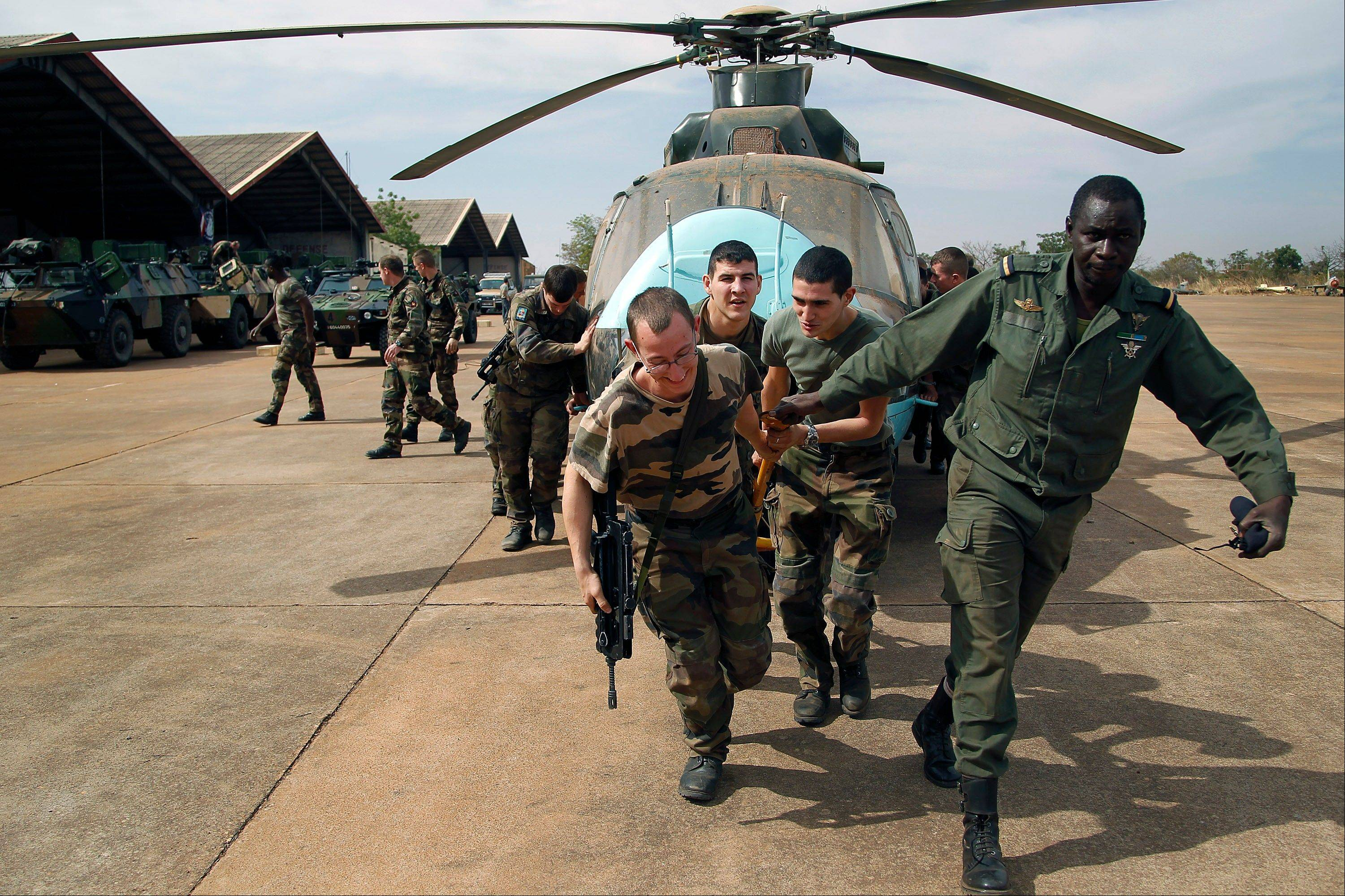 Malian soldiers helped by French troops, move a broken helicopter out a hangar to make room for more incoming troops at Bamako�s airport Tuesday.