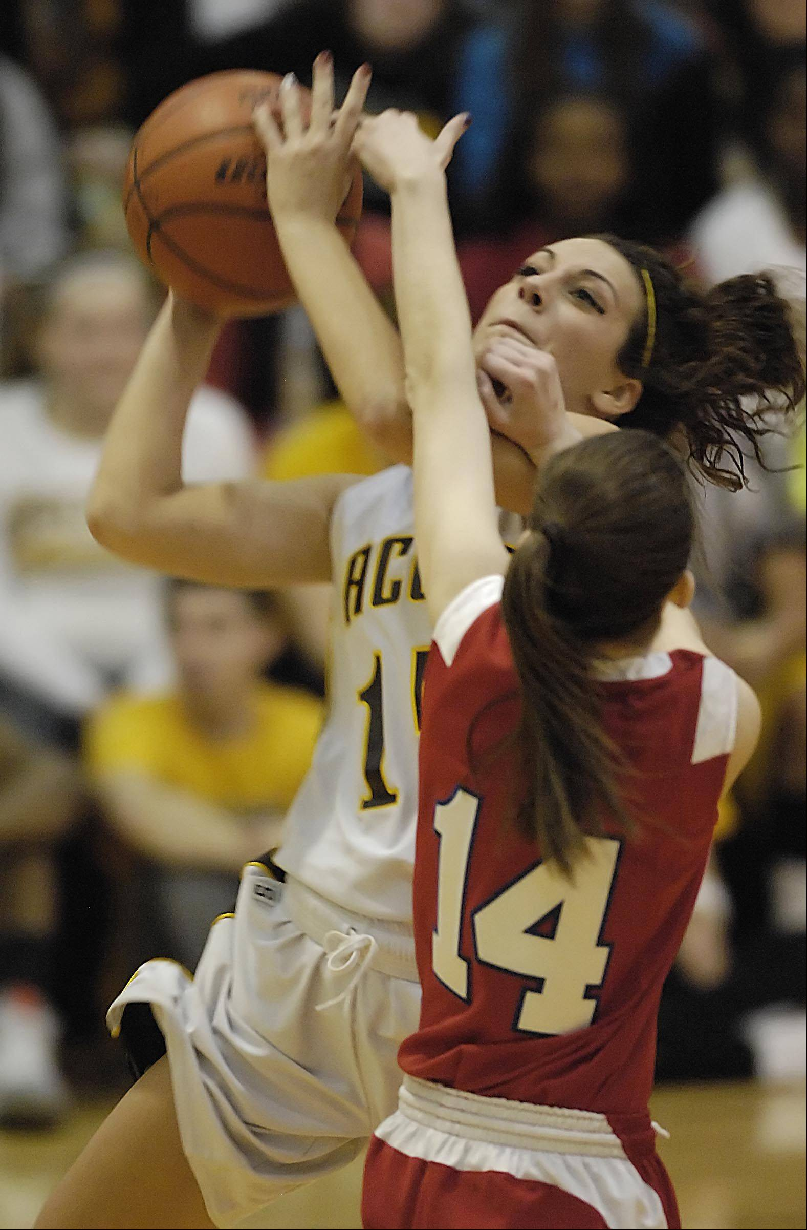 Jacobs� Payton Berg shoots around Dundee-Crown�s Melissa Barker Tuesday in Algonquin.