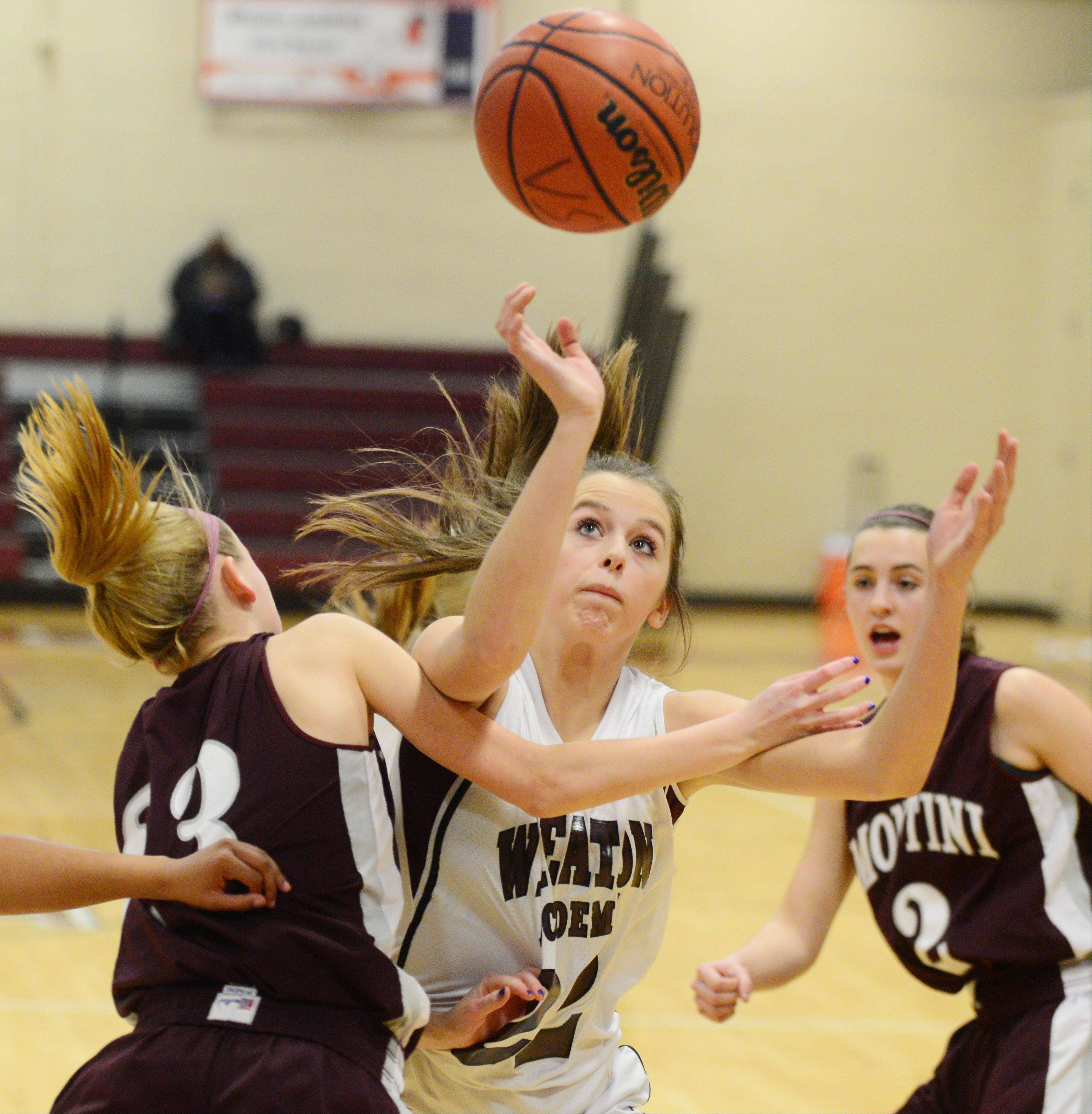Lea Kerstein of Montini,left, and Elizabeth Melby of Wheaton Academy go for a loose ball.