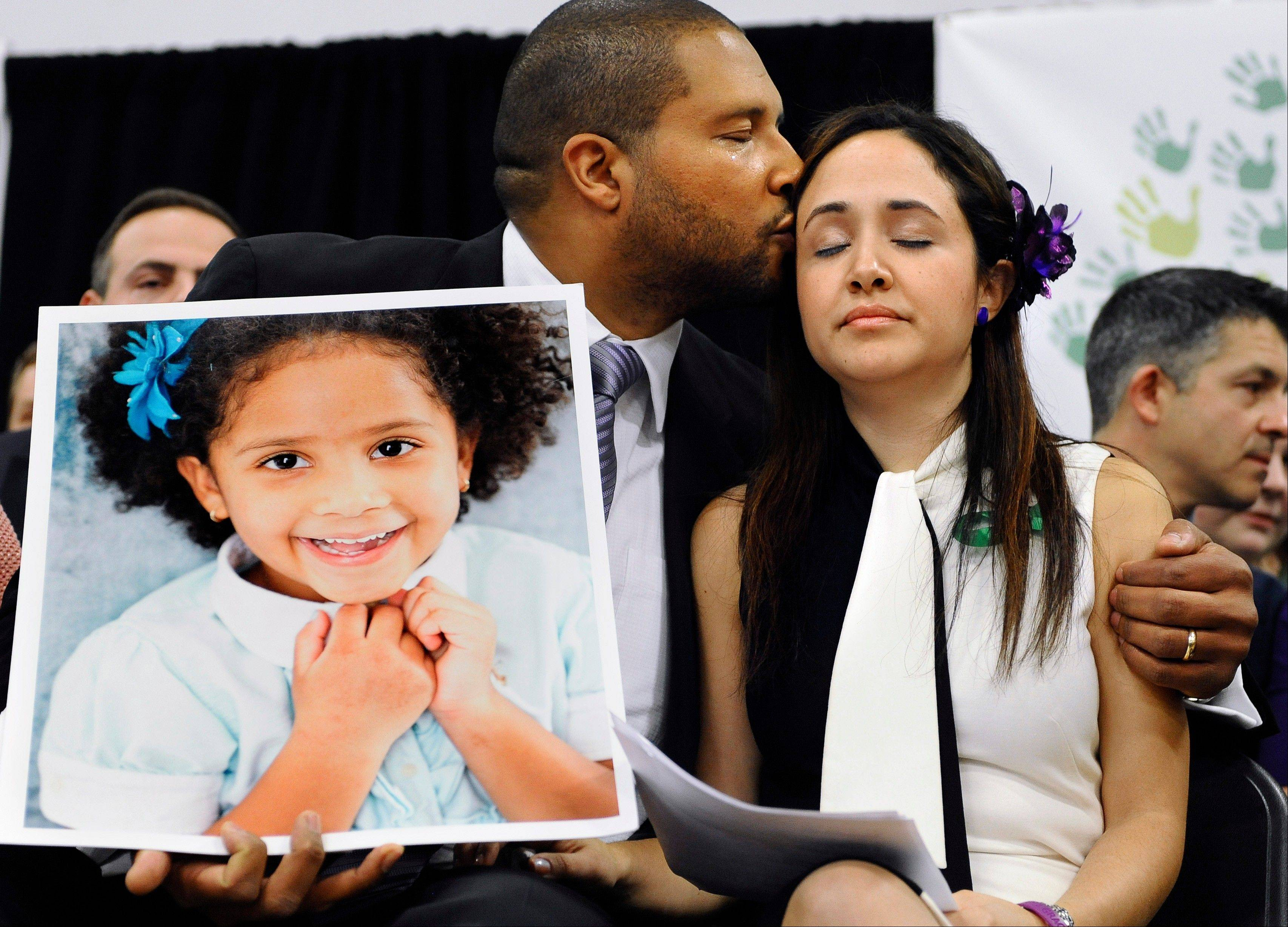 "Jimmy Greene, left, kisses his wife, Nelba Marquez-Greene, as he holds a portrait of their daughter, Sandy Hook School shooting victim Ana Marquez-Greene, at a news conference at Edmond Town Hall in Newtown, Conn., Monday. PBS announced Monday it will air a series of programs under the umbrella title ""After Newtown"" in February."