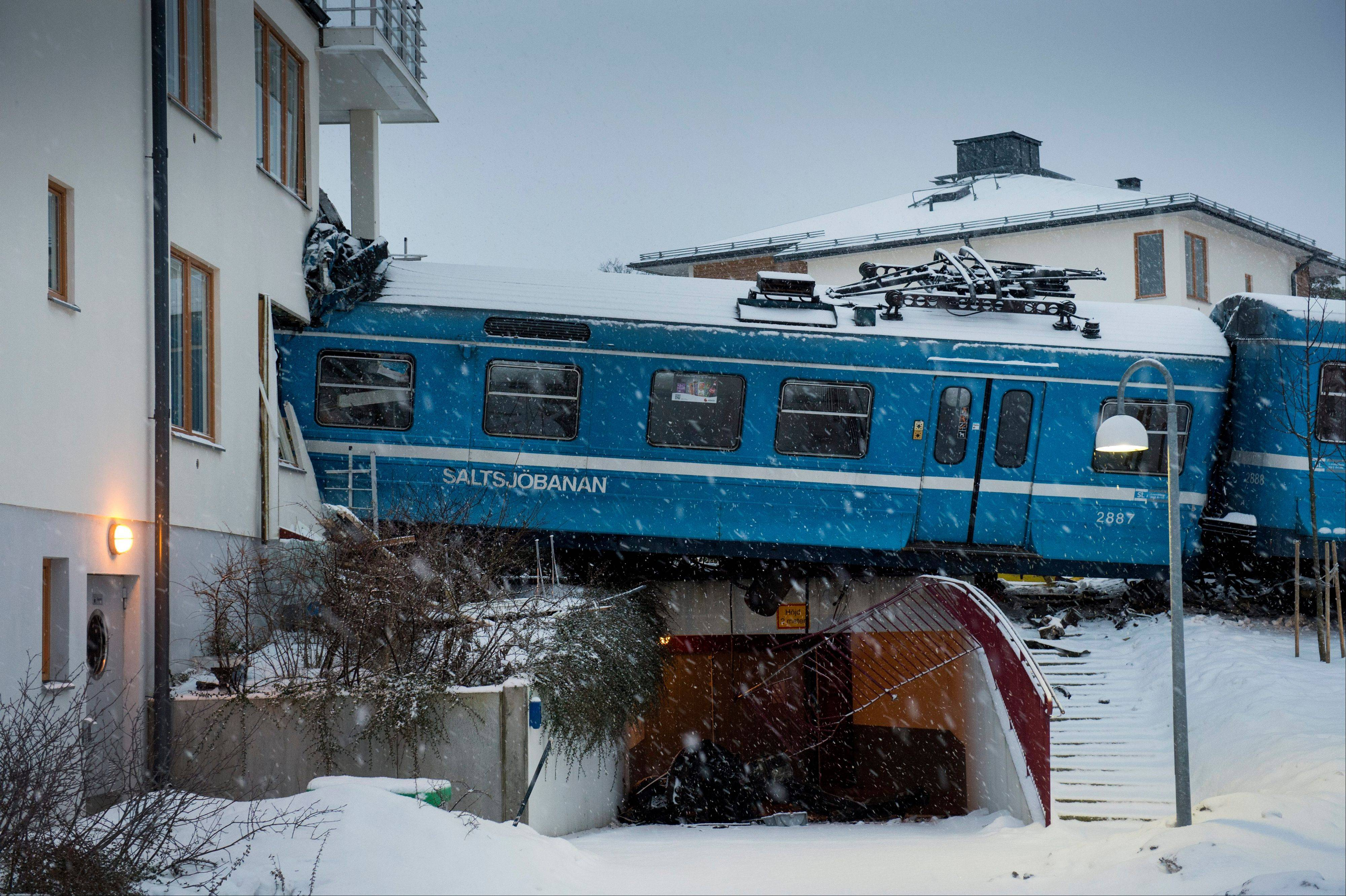 Derailed train that hangs on the edge of the track after it crashed into the side of a residential building in Saltsjobaden outside Stockholm, Tuesday Jan, 15, 2013. A woman obtained the keys to the train and drove it away before it crashed into the building. The woman was injured in the incident and there are no reports of injuries of people in the building.