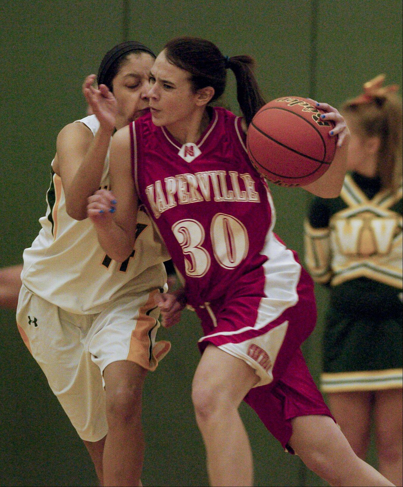 Naperville Central's Shannon Ryan drives past Waubonsie Valley's Andrea Colin during Monday's game in Aurora.