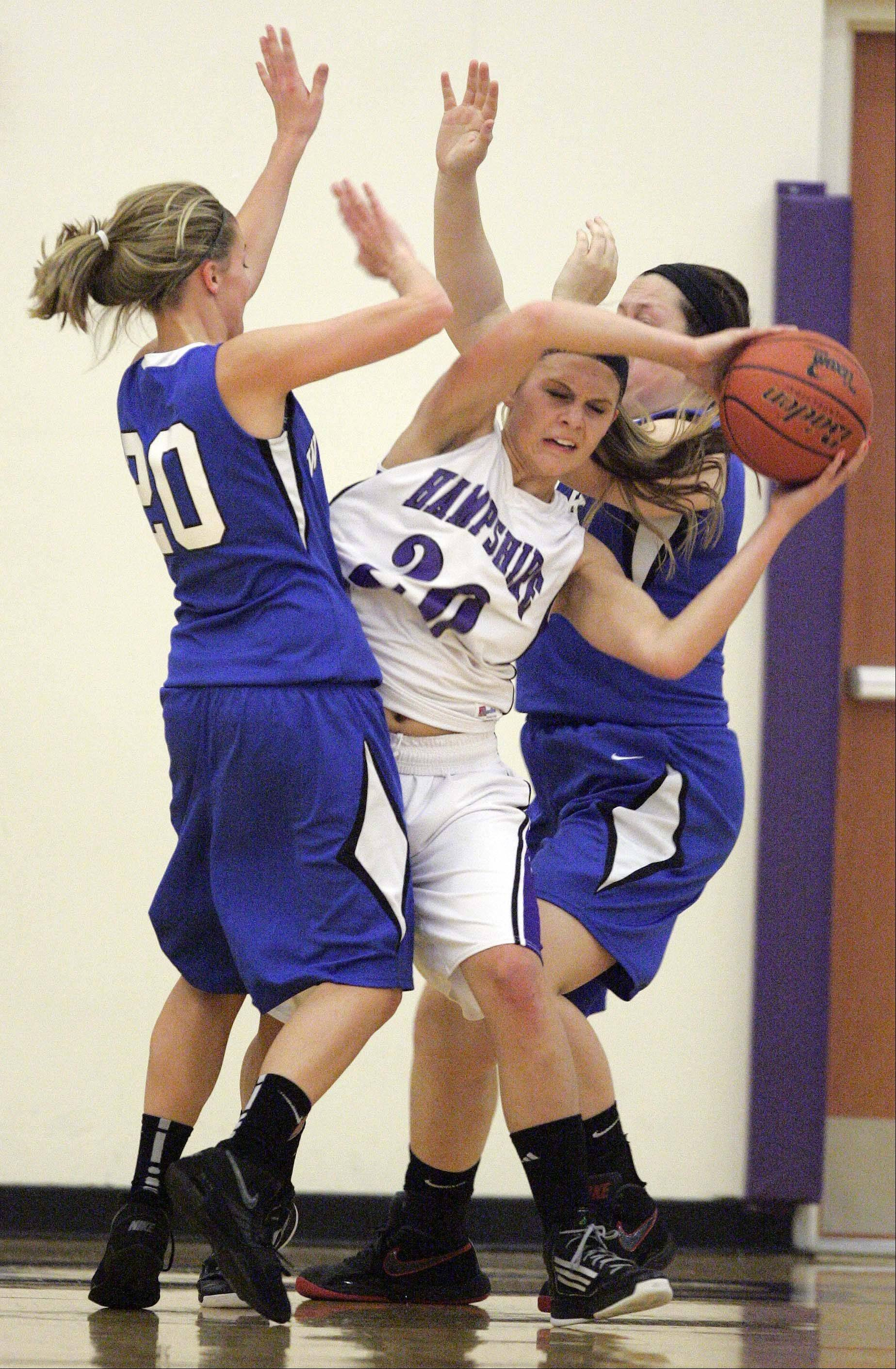 Hampshire's Lizzy Panzica, 20, slips between Woodstock's Sydney Haulotte, 20, and AMber Roberts, 44, during Saturday's game.