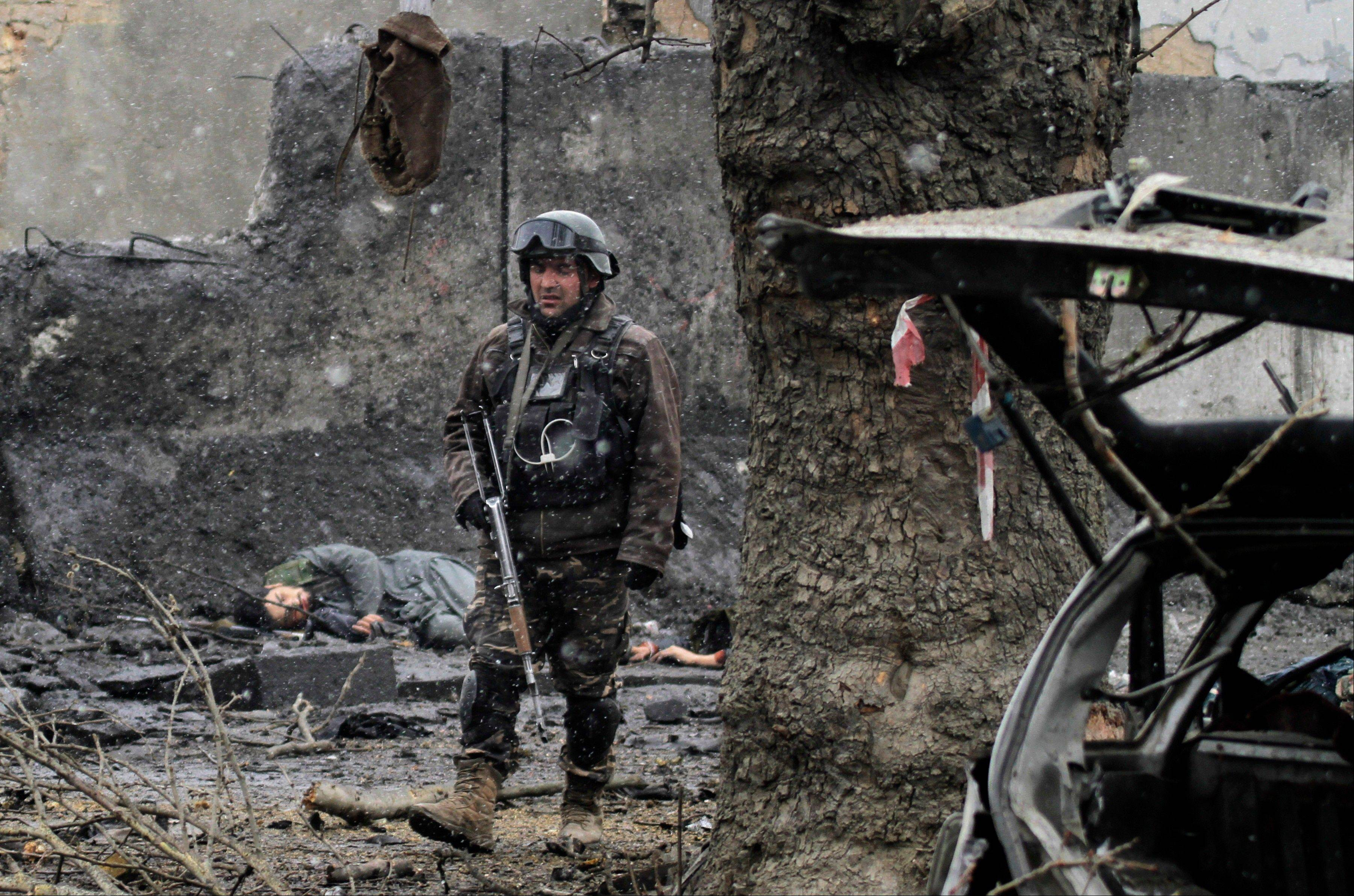 An Afghan security guard walks at the scene after an attack by militants Wednesday in Kabul, Afghanistan.
