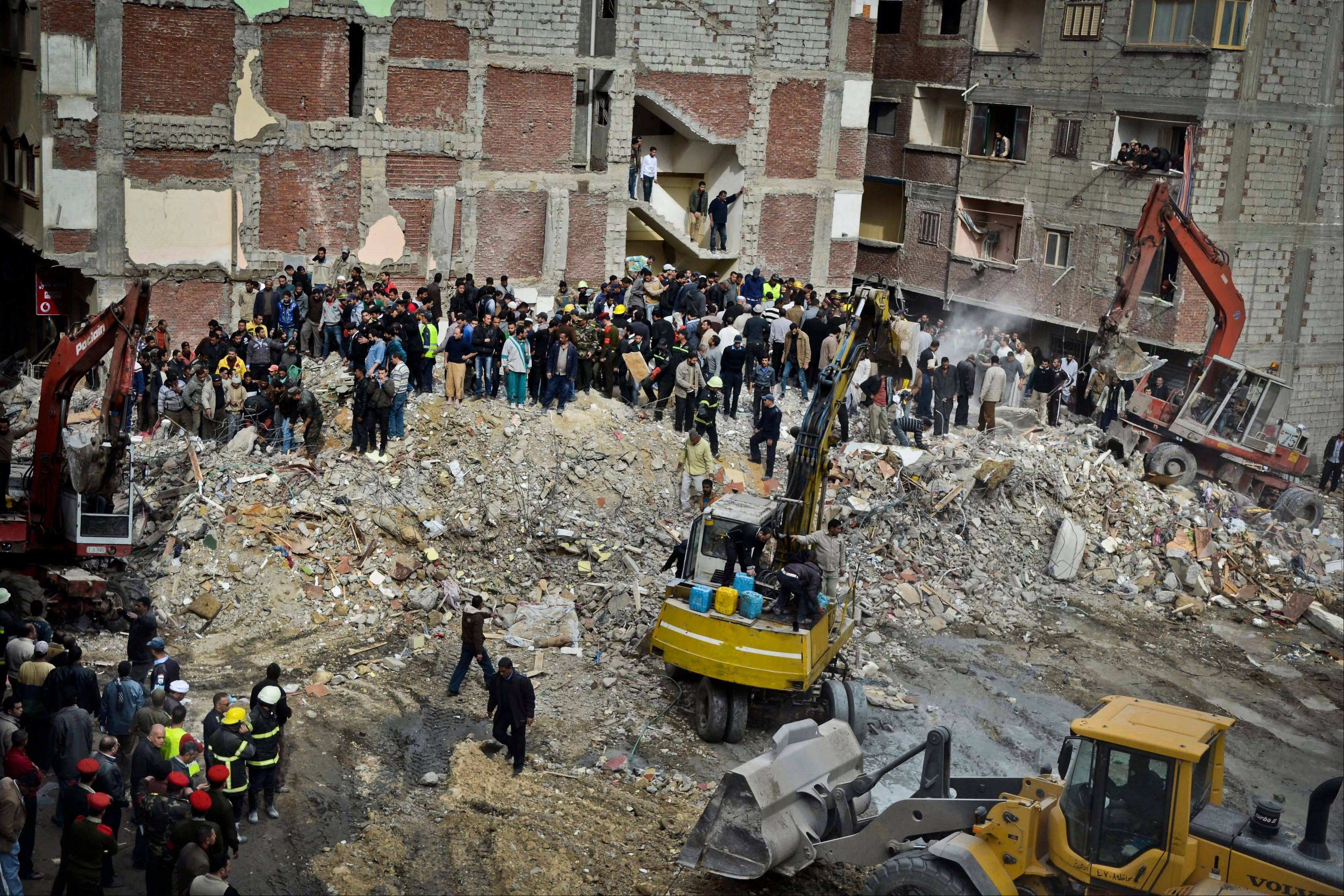 Egyptians stand in rubble Wednesday after an eight-story building collapsed in Alexandria, Egypt.