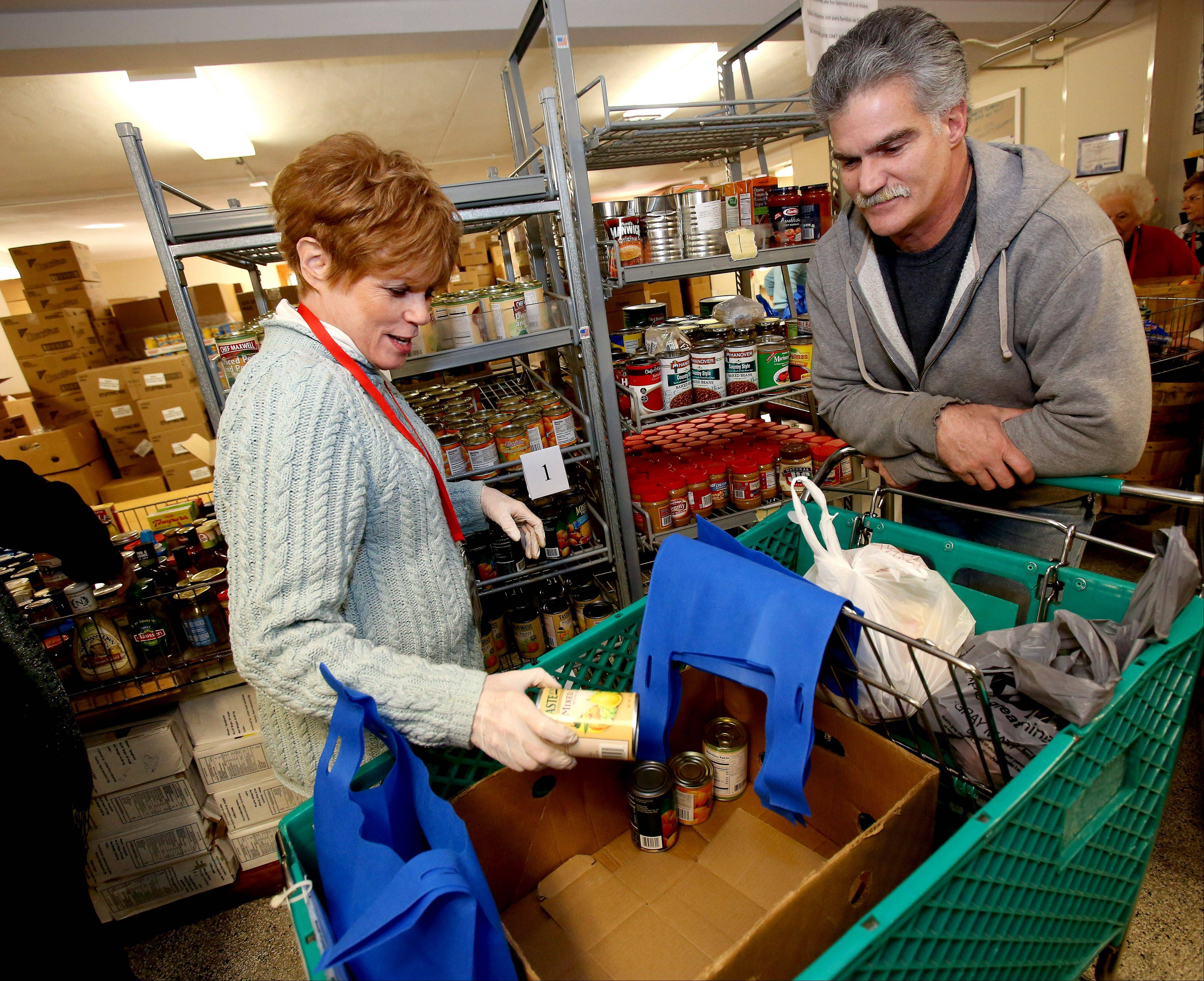 Volunteer Anita Pontious puts some cans in the cart for Richard Hale of Glen Ellyn during his visit to the food pantry at the People's Resource Center in Wheaton Tuesday.