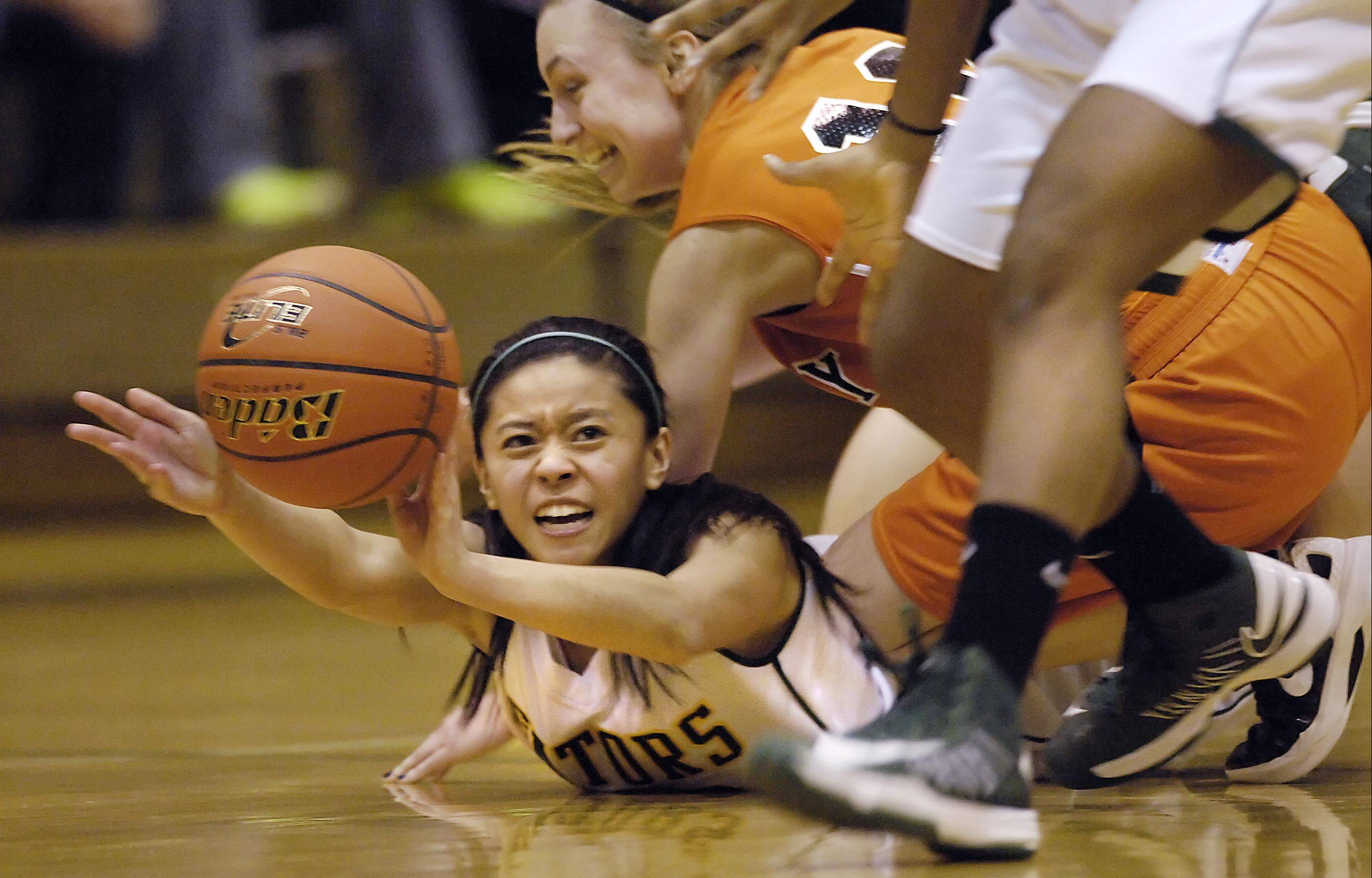 Crystal Lake South�s Gaby De Jesus (22) passes to teammate Kianna Clark as McHenry�s Laura D�Angelo falls on her back Wednesday in Crystal Lake.