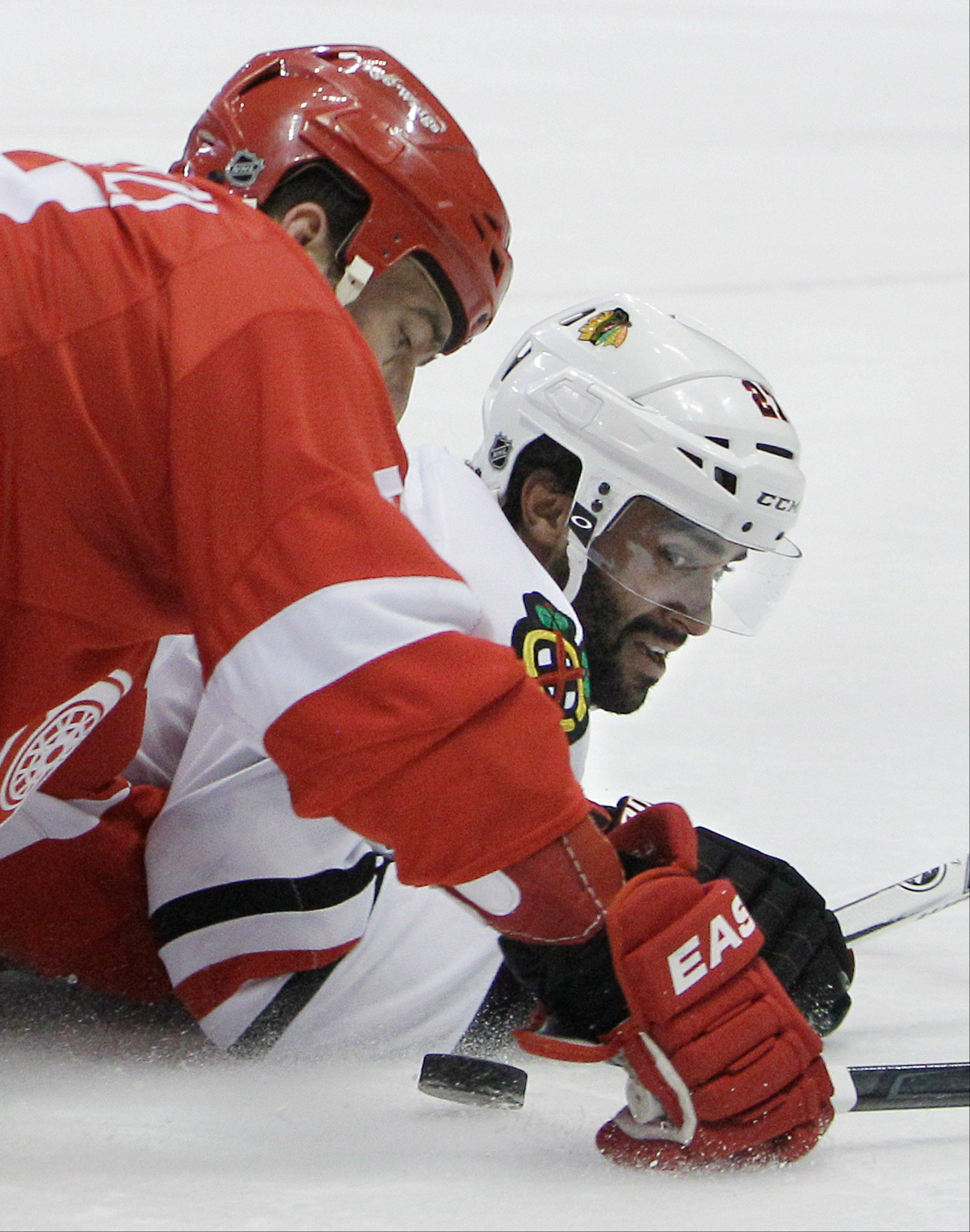 Detroit Red Wings right wing Todd Bertuzzi (44) and Chicago Blackhawks defenseman Johnny Oduya (27) of Sweden eye the puck during the third period of an NHL hockey game in Detroit, Sunday, March 4, 2012. (AP Photo/Carlos Osorio)