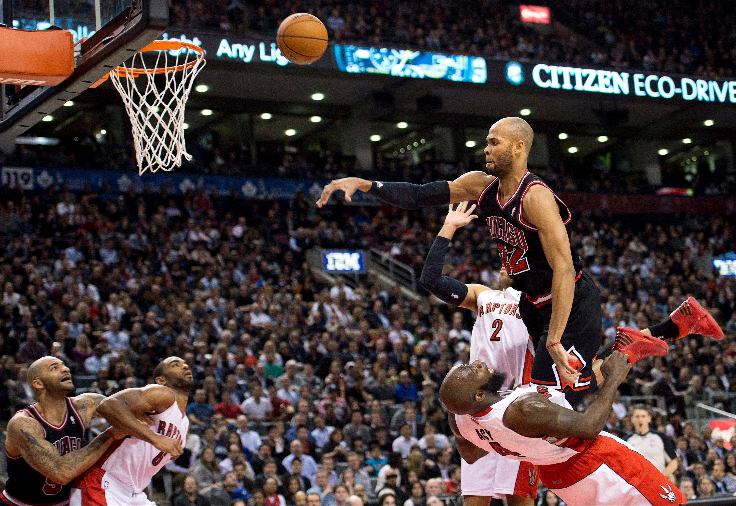 Bulls forward Taj Gibson (22) knocks down Toronto Raptors forward Quincy Acy, bottom right, during the second half of an NBA basketball game, Wednesday, Jan. 16, 2013, in Toronto. The Bulls won 107-105 in overtime.
