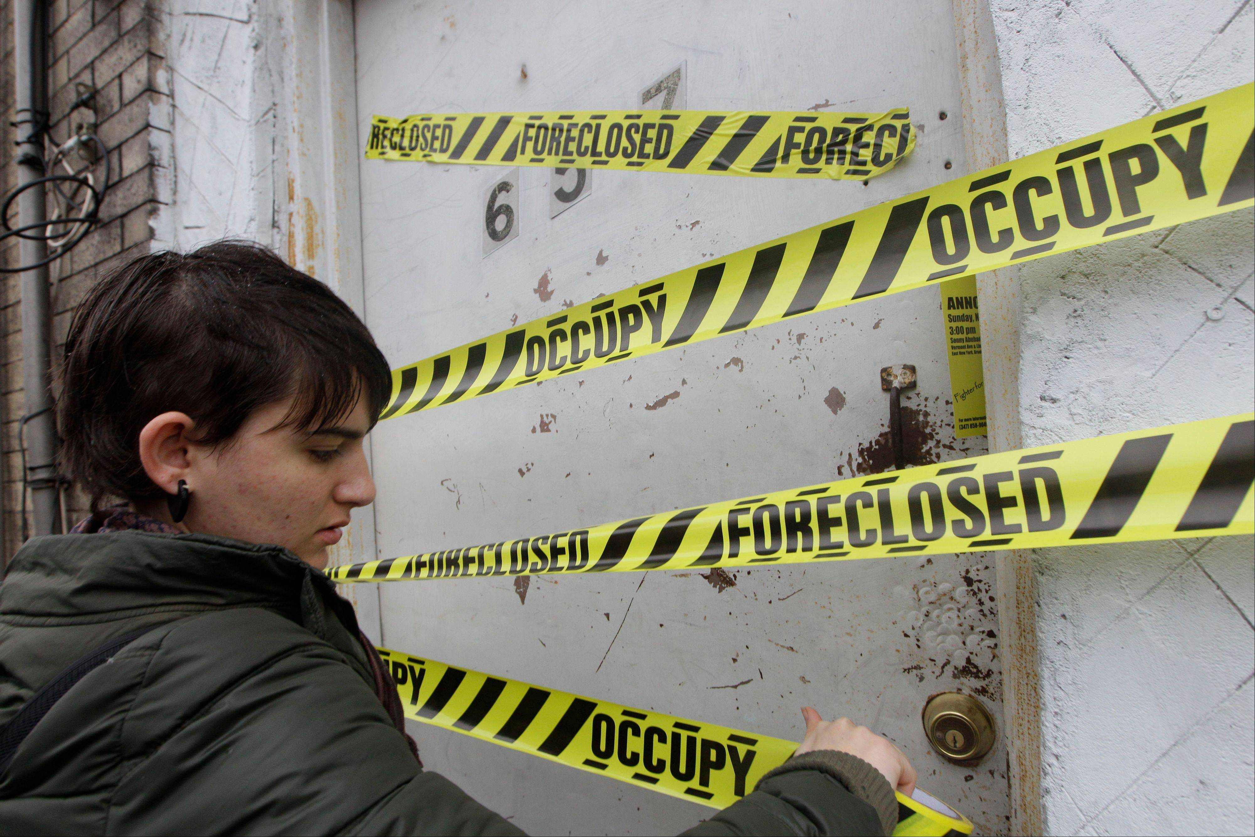 An Occupy Wall Street activist places tape on a boarded up house during a tour of foreclosed homes in the East New York neighborhood of the Brooklyn borough of New York.