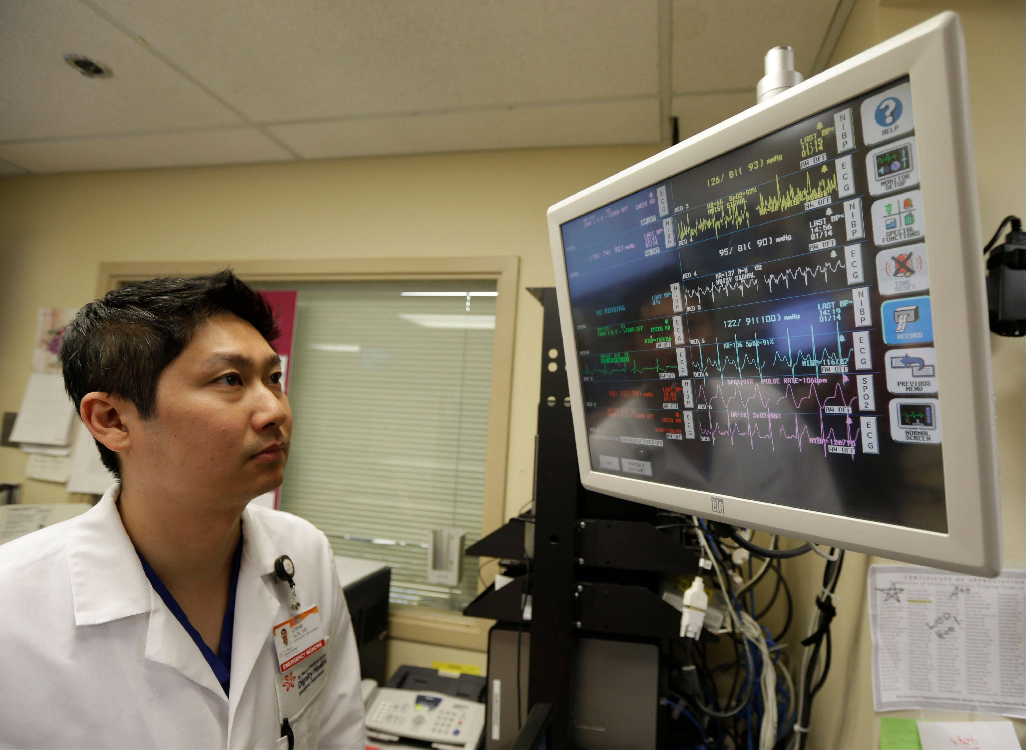Dr. Steve Sun looks over a heart monitor display in the emergency room at St. Mary's Medical Center in San Francisco.