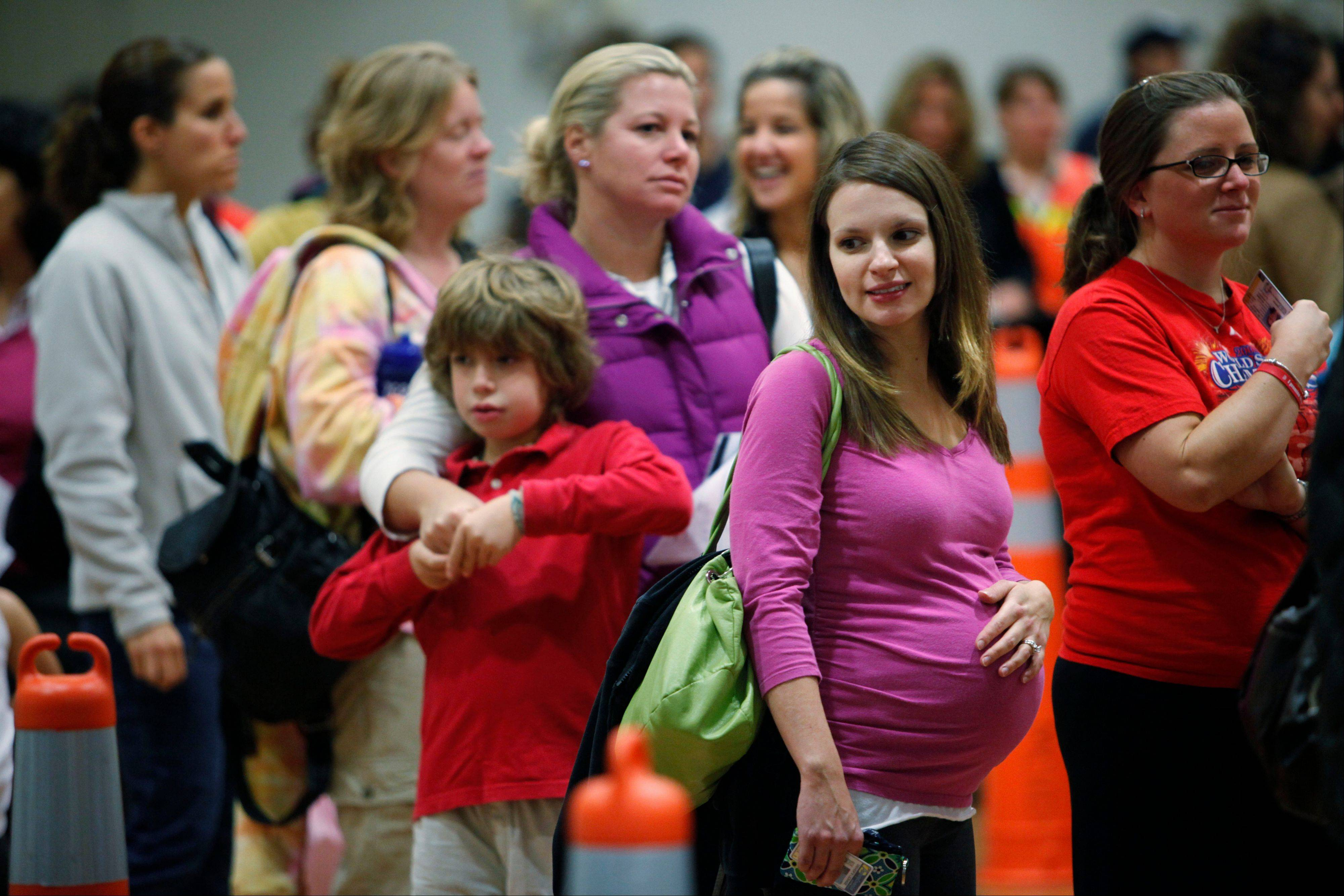 Associated Press/Thursday, Oct. 29, 2009Nicole Andreacchio, second right, who is seven months pregnant, waits in line to receive the swine flu vaccine from the Montgomery County Health Department at Congregation Beth Or in Maple Glen, Pa.