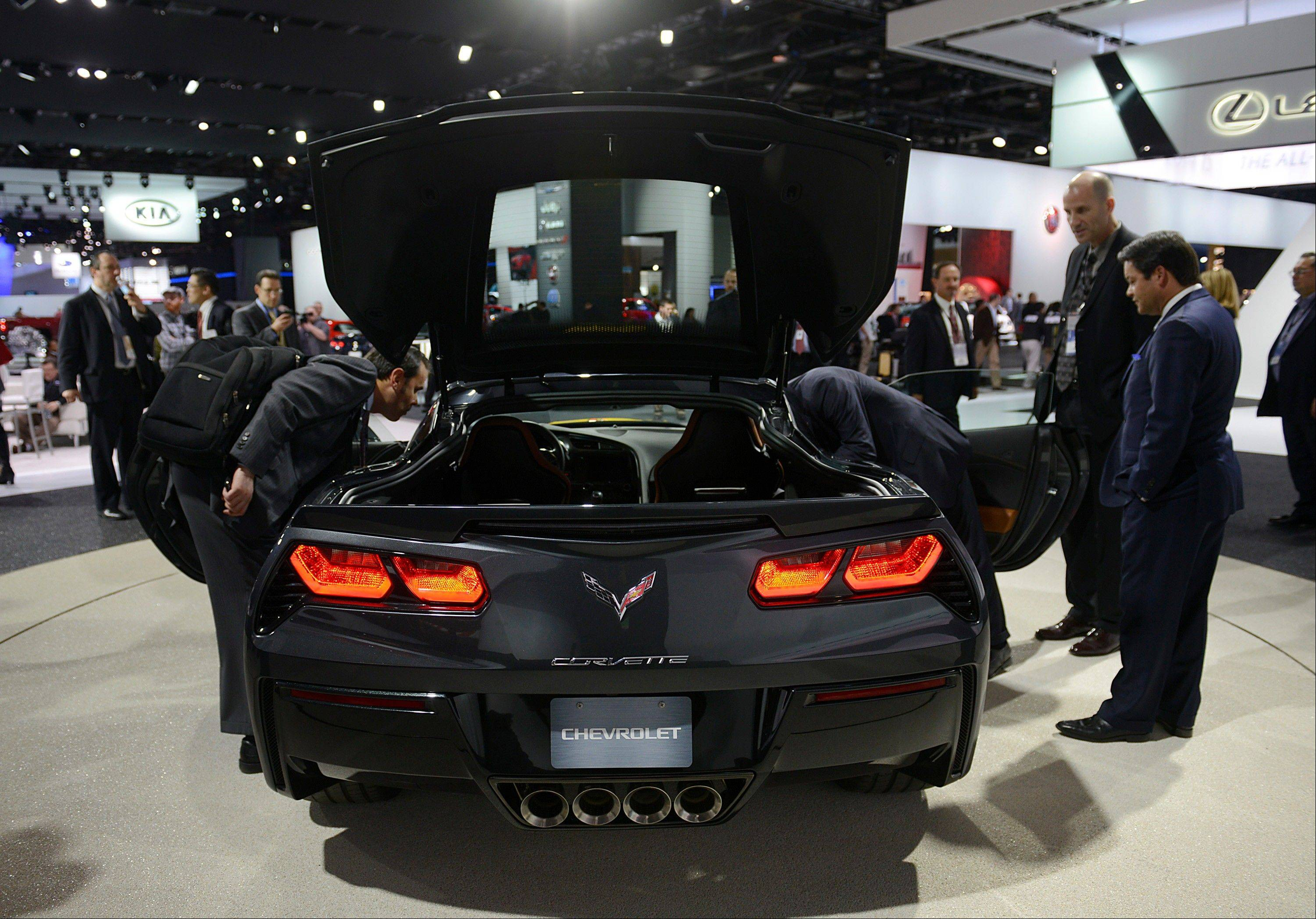 Attendees view the 2014 Chevrolet Corvette Stingray during the 2013 North American International Auto Show (NAIAS) in Detroit, Michigan, U.S., on Tuesday, Jan. 15, 2013. The Detroit auto show runs through Jan. 27 and will display over 500 vehicles, representing the most innovative designs in the world.
