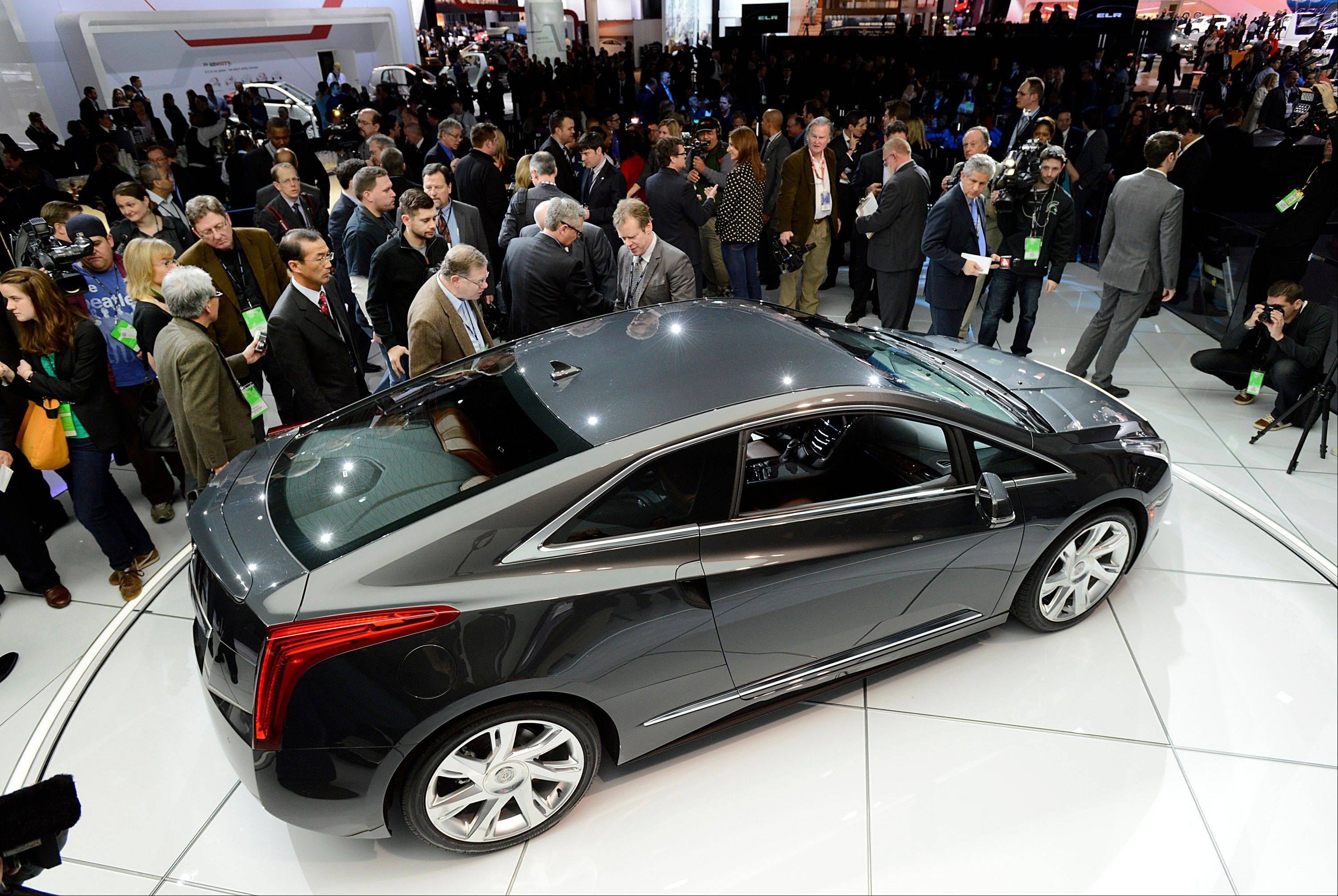 Members of the media view the General Motors Co. (GM) Cadillac ELR coupe vehicle after the unveiling at the 2013 North American International Auto Show (NAIAS) in Detroit, Michigan, U.S., on Tuesday, Jan. 15, 2013. The Detroit auto show runs through Jan. 27 and will display over 500 vehicles, representing the most innovative designs in the world.