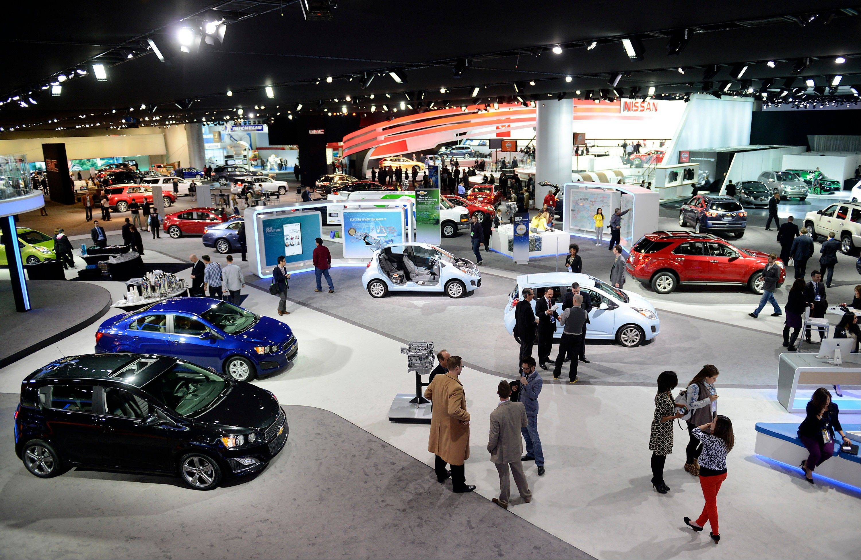 Attendees visit booths during the 2013 North American International Auto Show (NAIAS) in Detroit, Michigan, U.S., on Tuesday, Jan. 15, 2013. The Detroit auto show runs through Jan. 27 and will display over 500 vehicles, representing the most innovative designs in the world.
