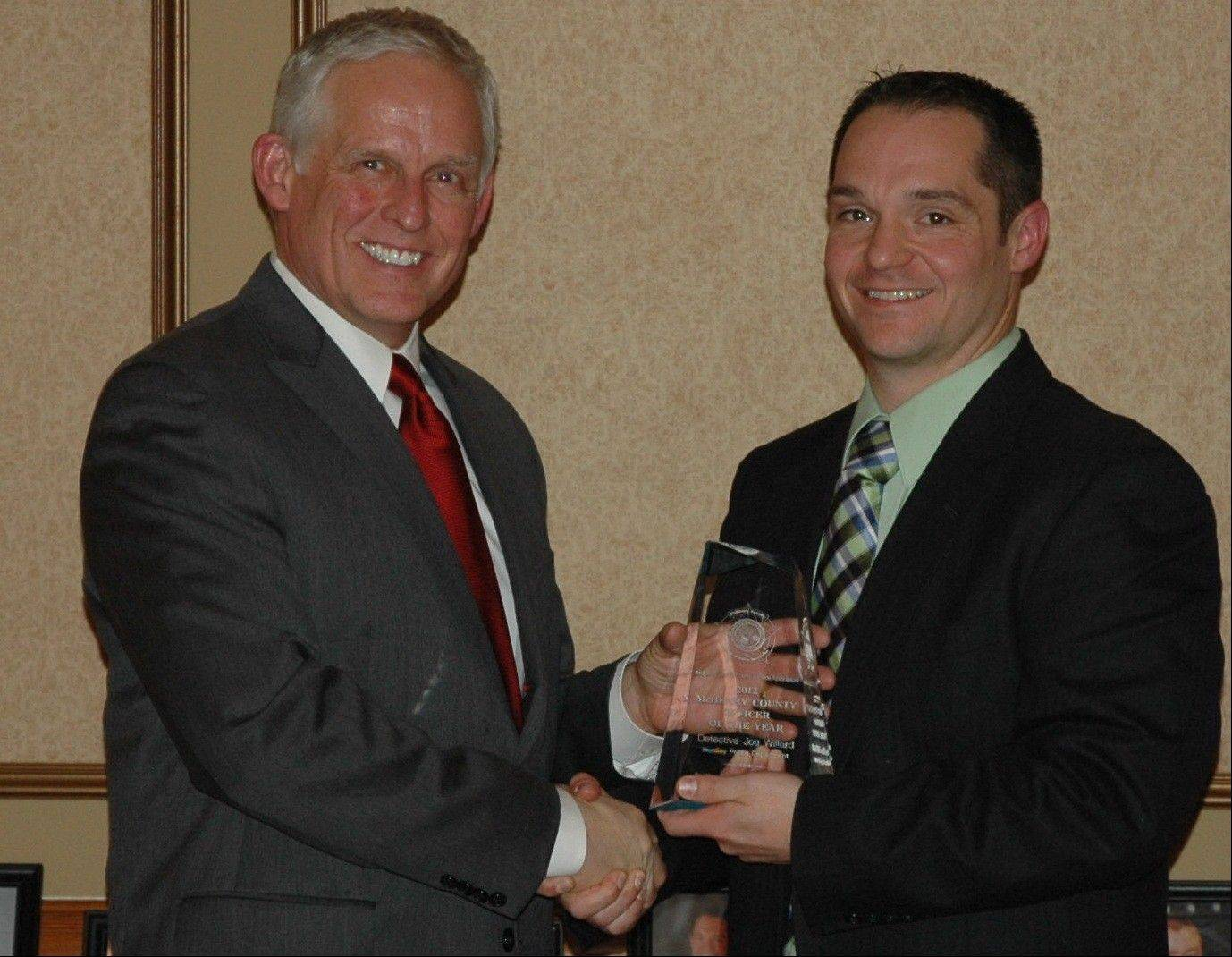 Huntley Police Chief John Perkins, left, president of the McHenry County Chiefs of Police Association, presents the group's annual officer of the year award to Huntley Detective Joe Willard.