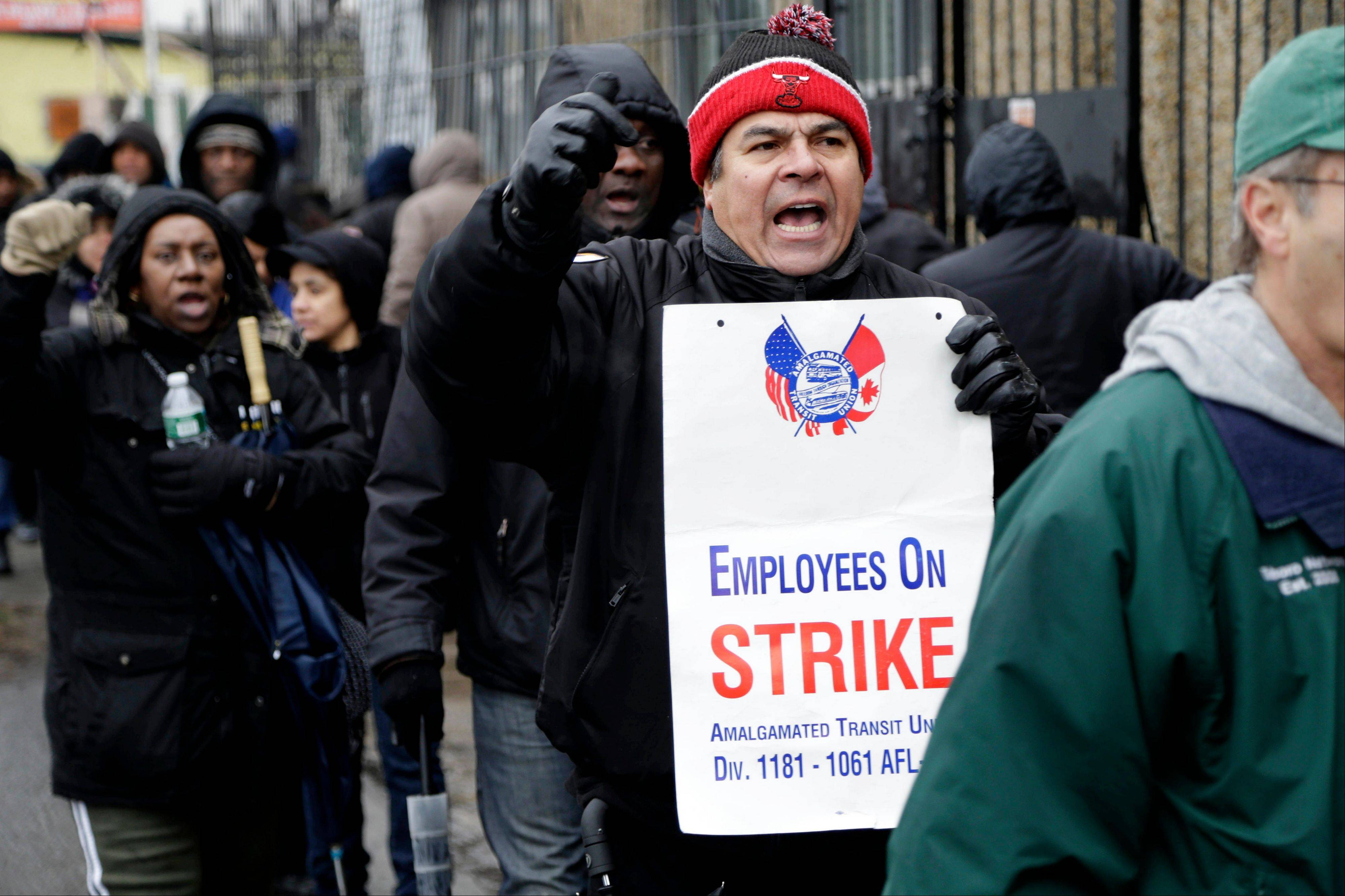 Bus drivers and supporters walk a picket line in front of a bus depot in New York, Wednesday, Jan. 16, 2013. More than 8,000 New York City school bus drivers and aides went on strike over job protection Wednesday morning, leaving some 152,000 students trying to find other ways to get to school.