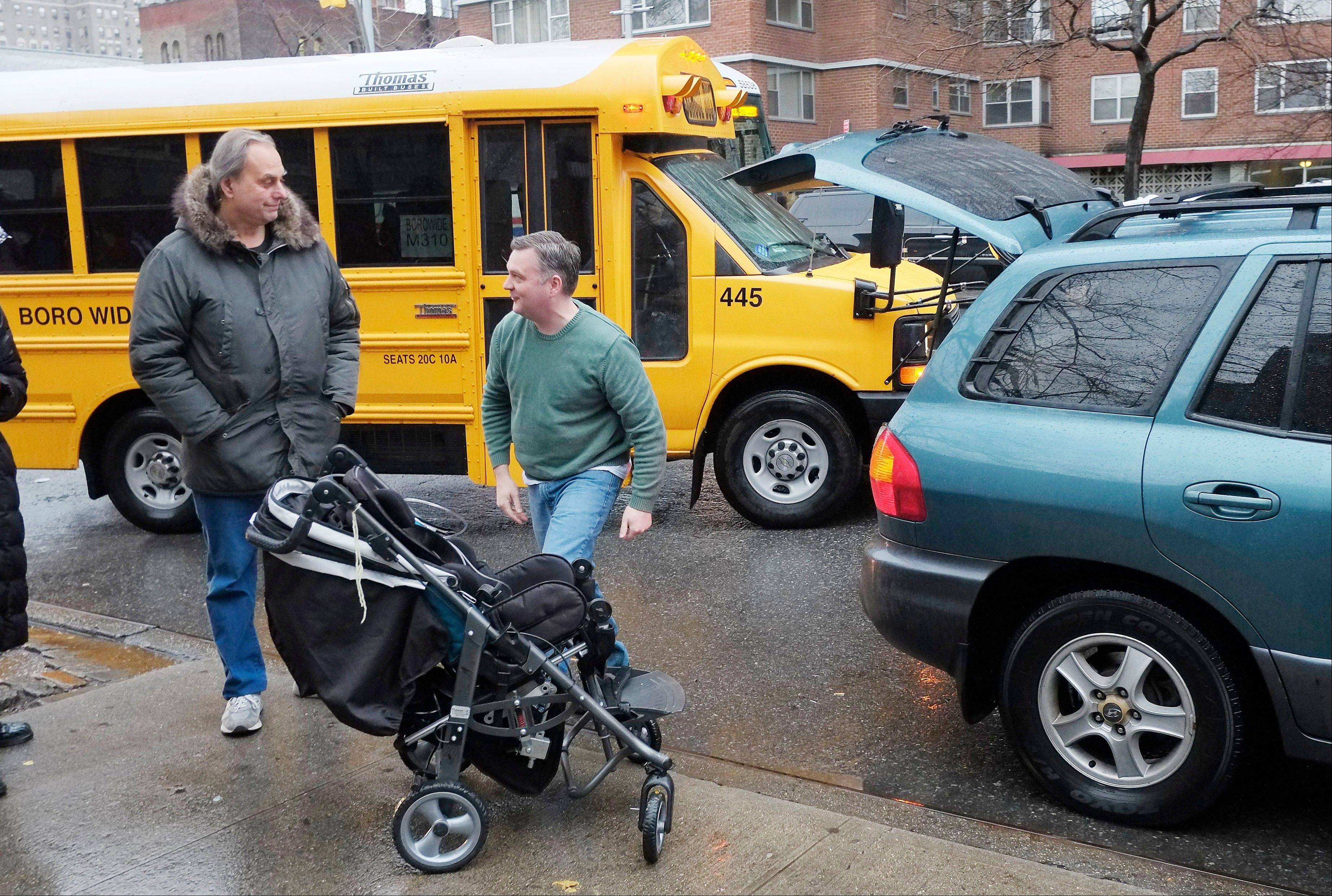 Peter Curry, center, unloads his daughter's wheelchair from his car after driving her to Public School 33, Wednesday, Jan. 16, 2013 in New York. She would normally be driven by school bus, according to her father.