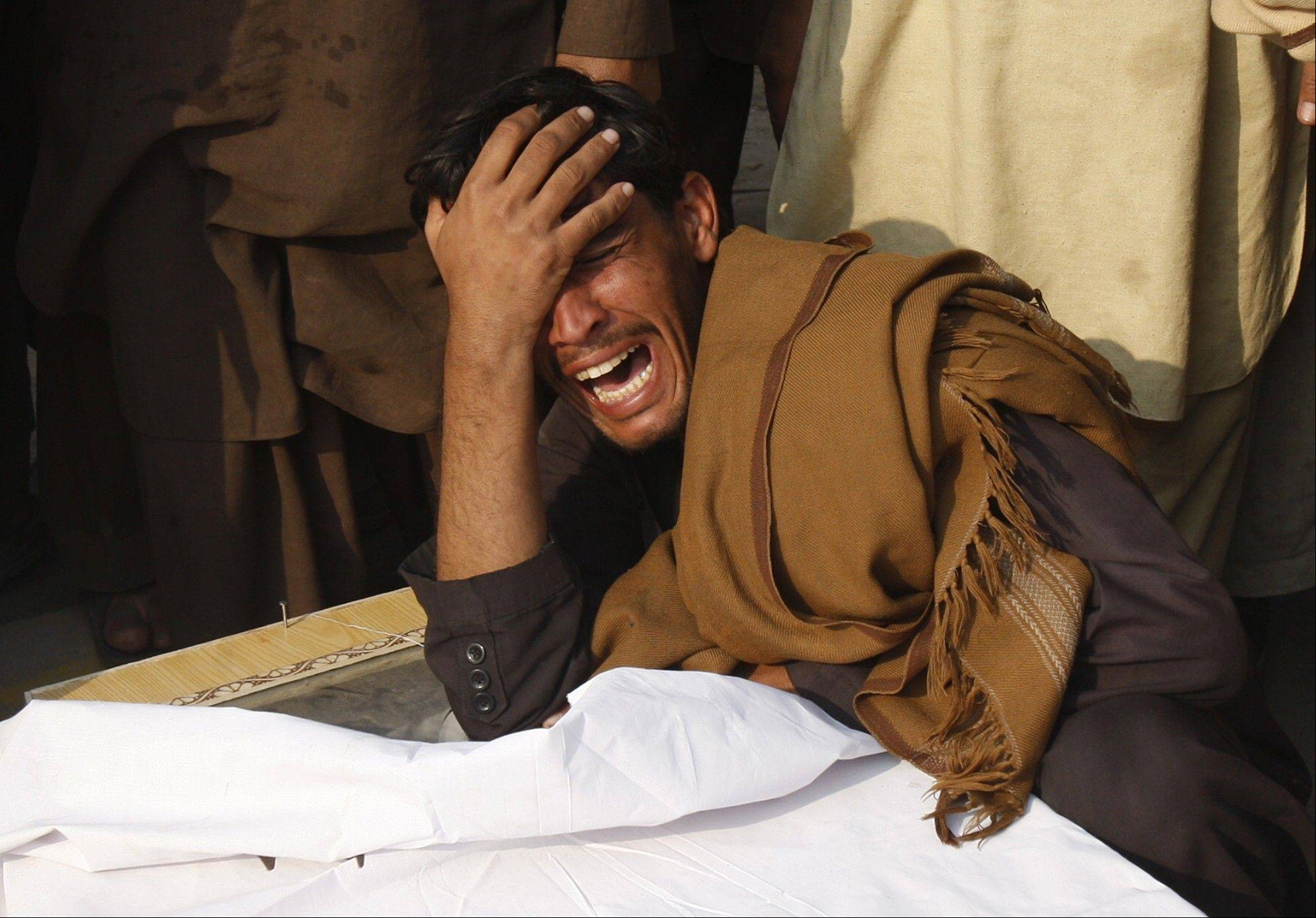 A man mourns the death of his family member in Peshawar, Pakistan, Wednesd