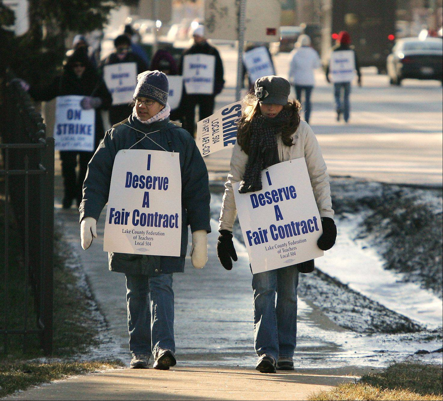 Grayslake Middle School teachers Pei Pump, left, and Nicole McRee join other teachers walking the picket line in the cold Wednesday near the school. Teachers from Grayslake Elementary District 46 went on strike after talks with the school board broke down Tuesday night.