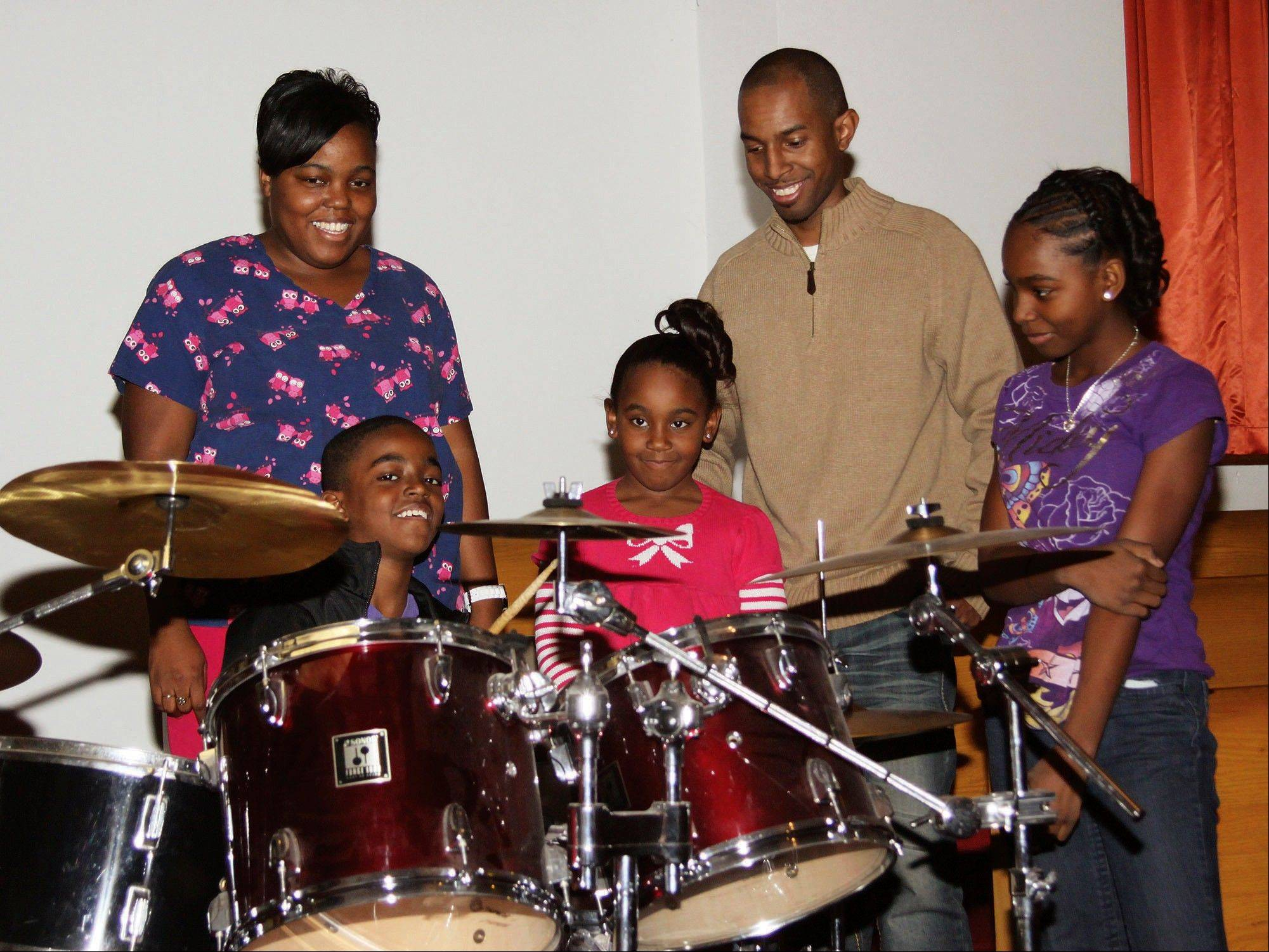 Maria and LaJason Parker, listen to their son Jayrin, 10, play the drums, as his sisters Jyah, 6, center, and Jalae, 12, also look on at the Greater Shiloh Baptist Church in Danville, Ill.