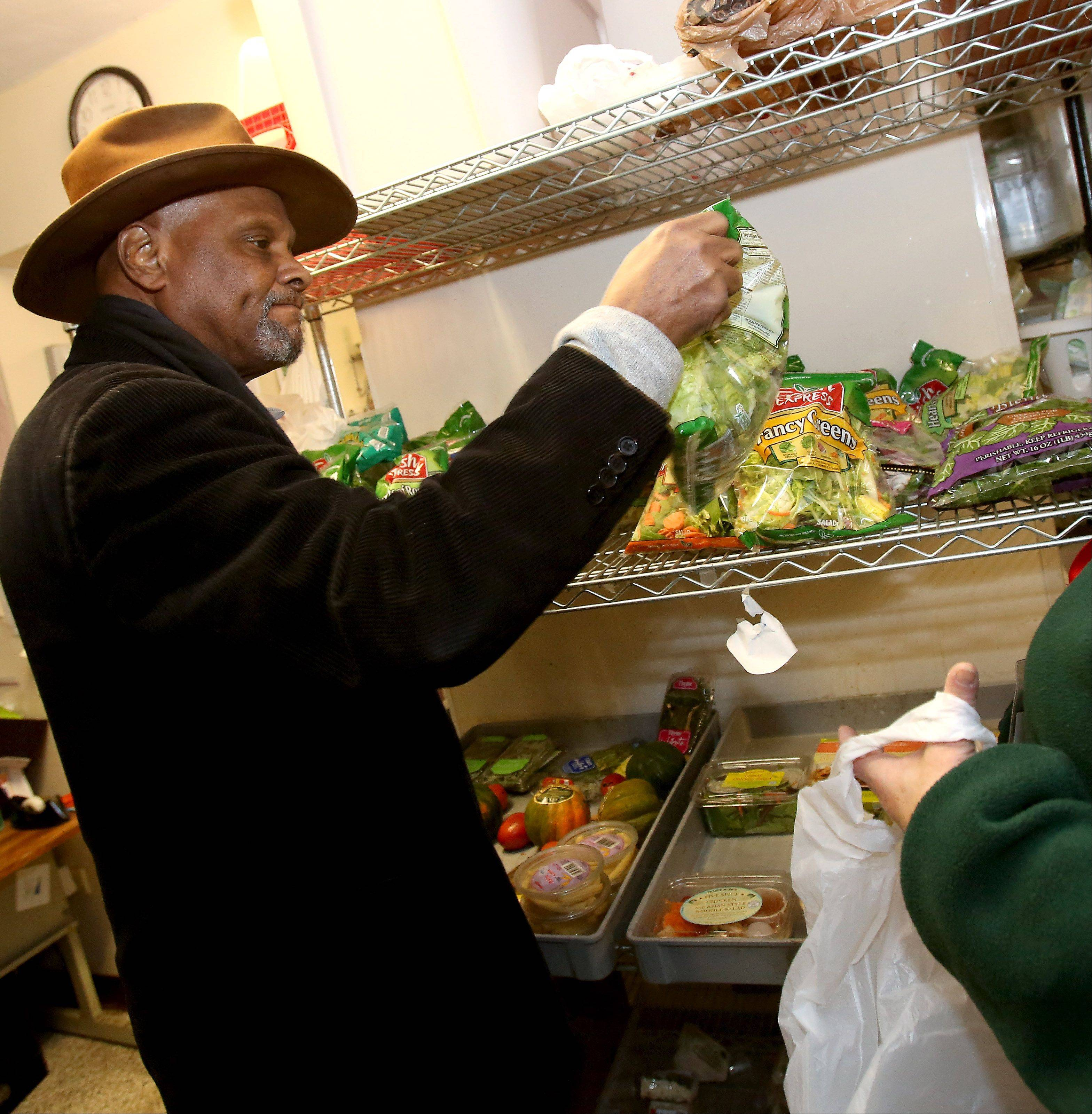 Vince Willis of Naperville picks out some lettuce during a visit to the food pantry at the People's Resource Center in Wheaton Tuesday.