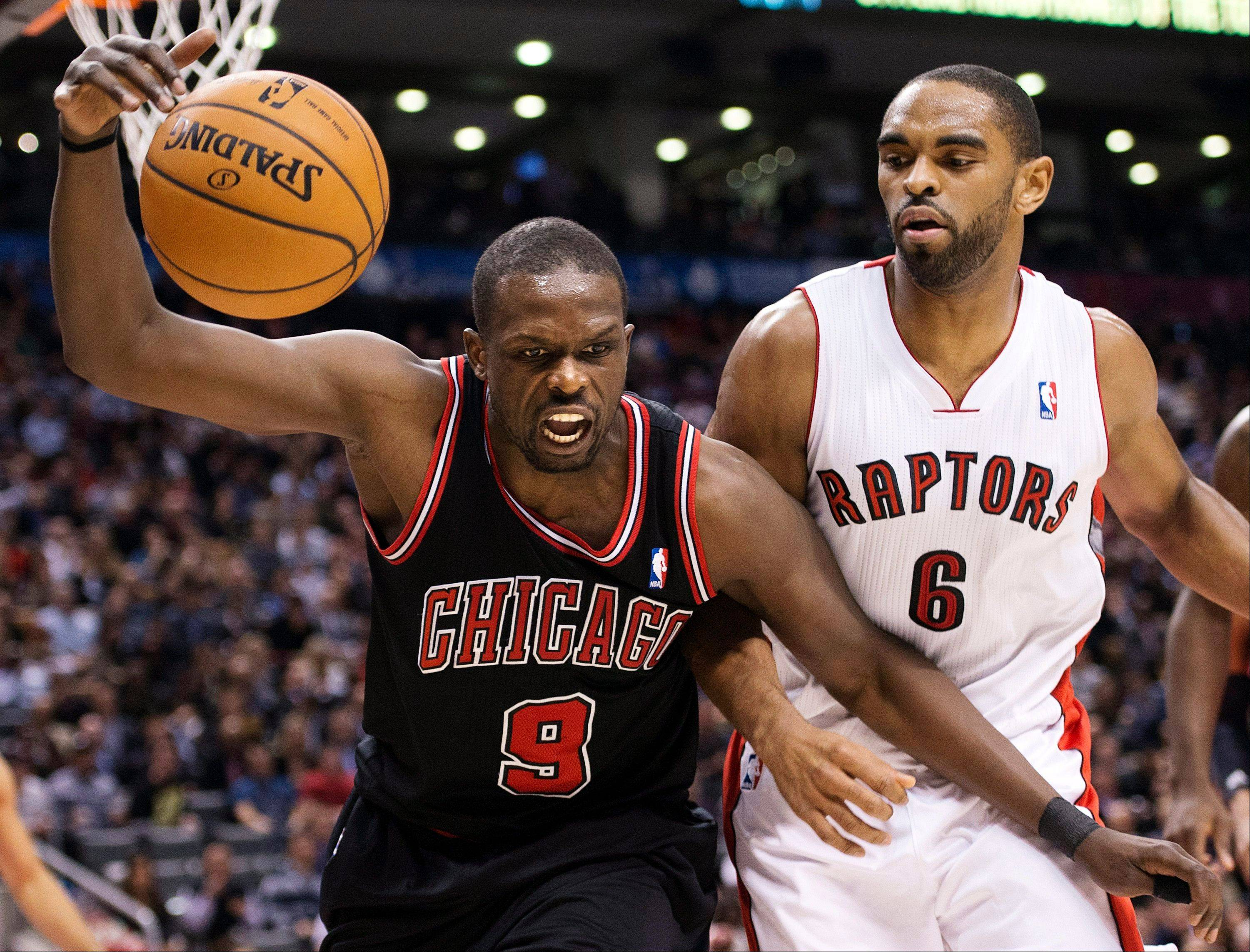 Toronto Raptors forward Alan Anderson (6) battles for a loose ball against Chicago Bulls forward Luol Deng (9) during the second half of an NBA basketball game, Wednesday, Jan. 16, 2013, in Toronto. The Bulls won 107-105 in overtime.