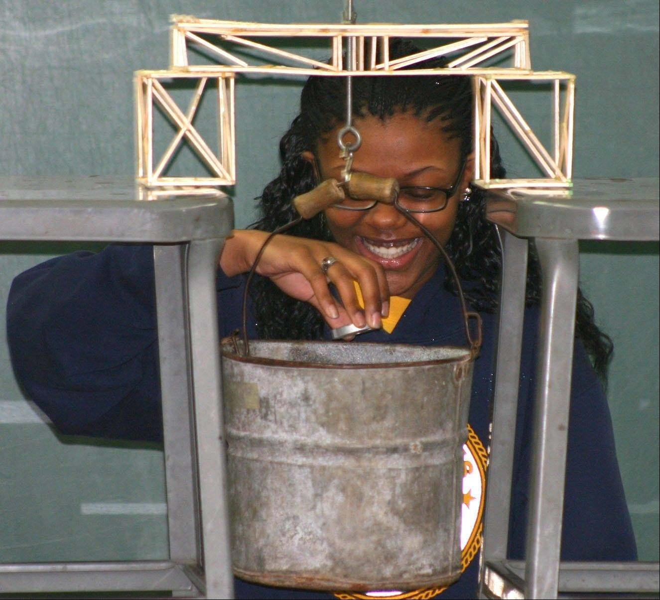 Mooseheart's Kyshona Dunn smiles as she prepares to add another weight to the bucket in the school's 27th annual bridge-breaking competition.