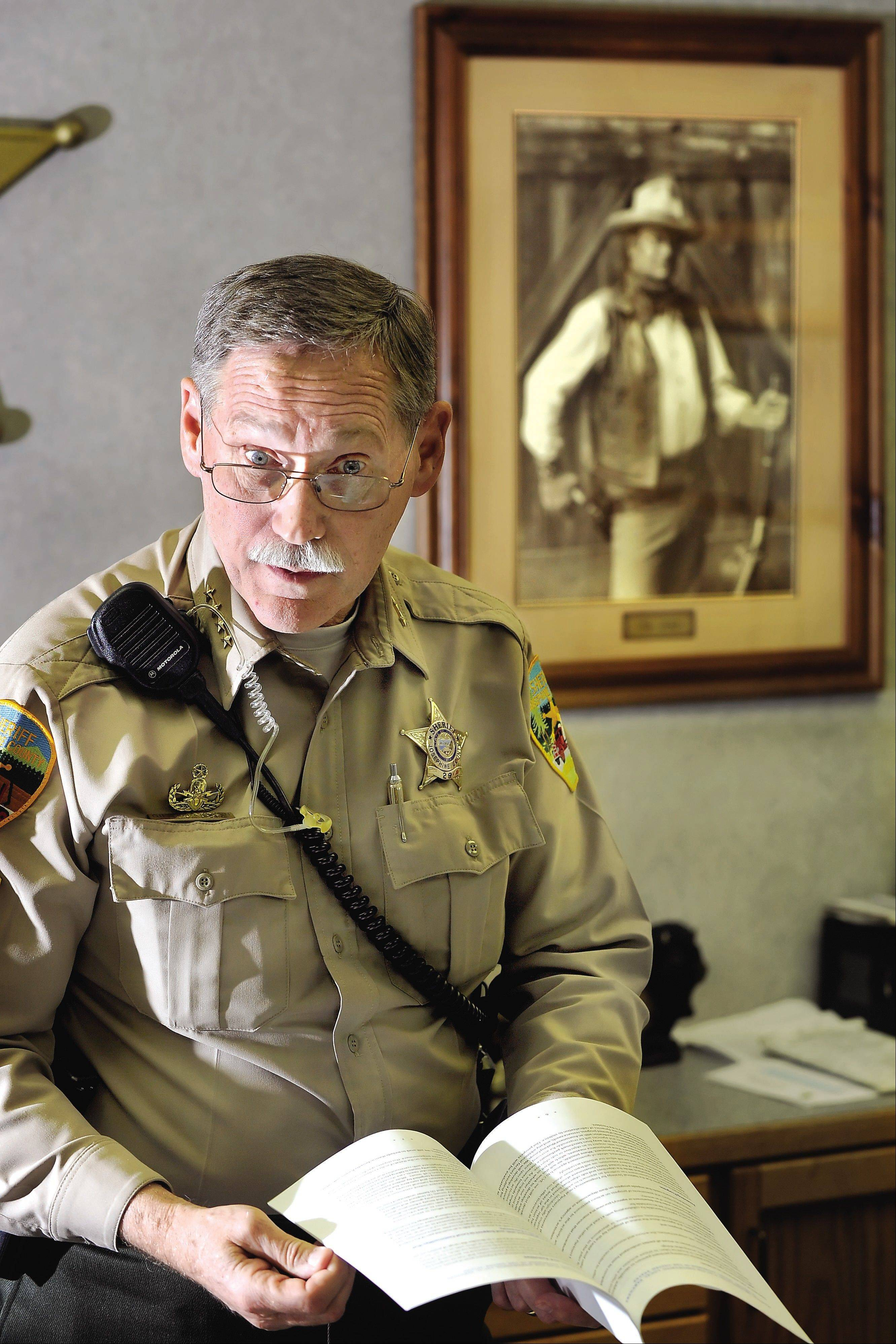 Josephine County Sheriff Gil Gilbertson stands in his office in Grants Pass, Ore. Gilbertson is one of a growing number of rural sheriffs and lawmakers vowing to ignore any new gun control legislation, or even make it a crime for federal officials to enforce federal gun policy.