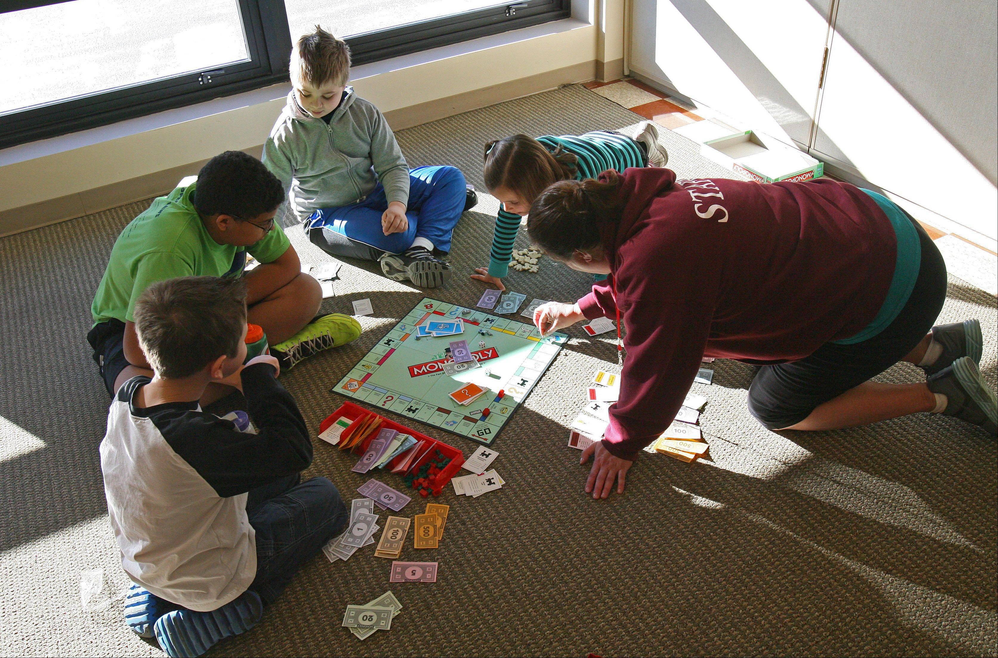 "Lynn Wells, right, plays Monopoly with children attending what's dubbed ""strike camp"" where she works at Grayslake Park District's recreation center. Grayslake Elementary District 46 teachers were on strike again Thursday, so the camp was devised to give idle children something to do."