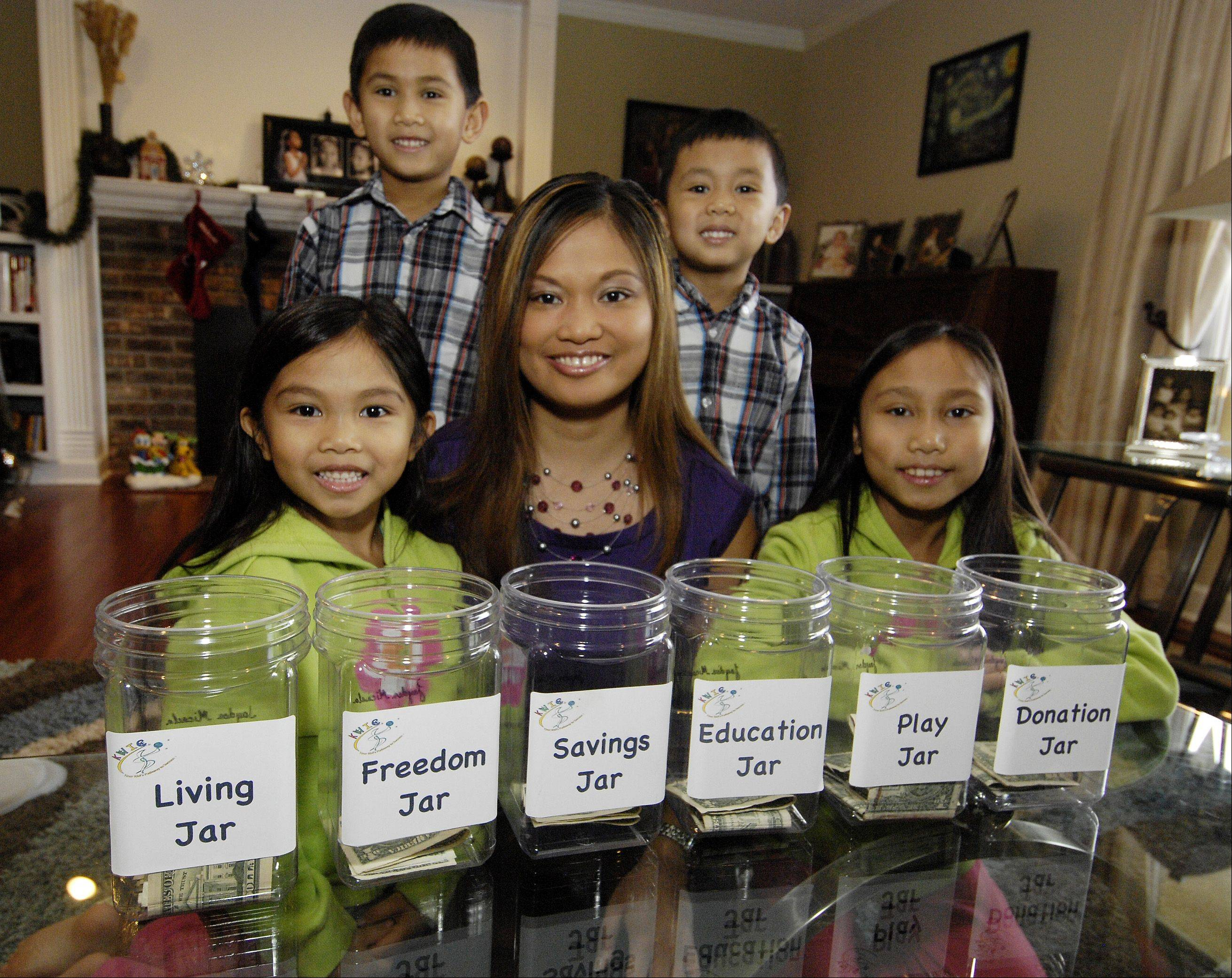 Melanie Jane Nicolas and her children, Jayden, 5, Dylan, 6, Dean, 4, and Jardeleza Javier, 9, show the six labeled money jars the kids use to divide their money.